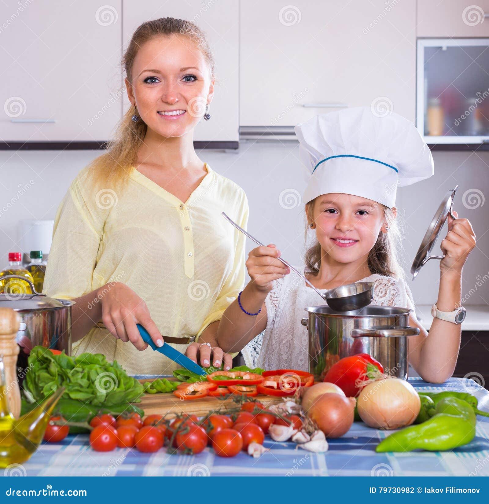 Mujer y muchacha que cocinan los veggies