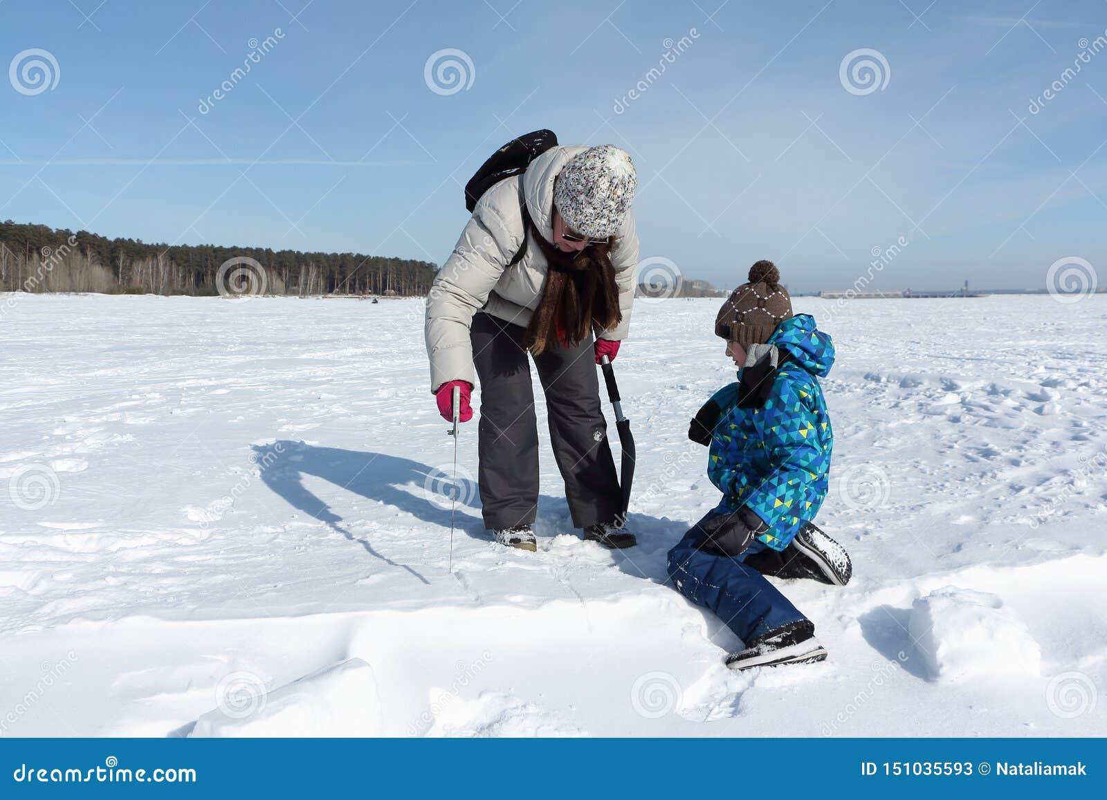 Mujer y un niño pequeño que asierra un bloque de la nieve para construir un iglú, Novosibirsk, Rusia