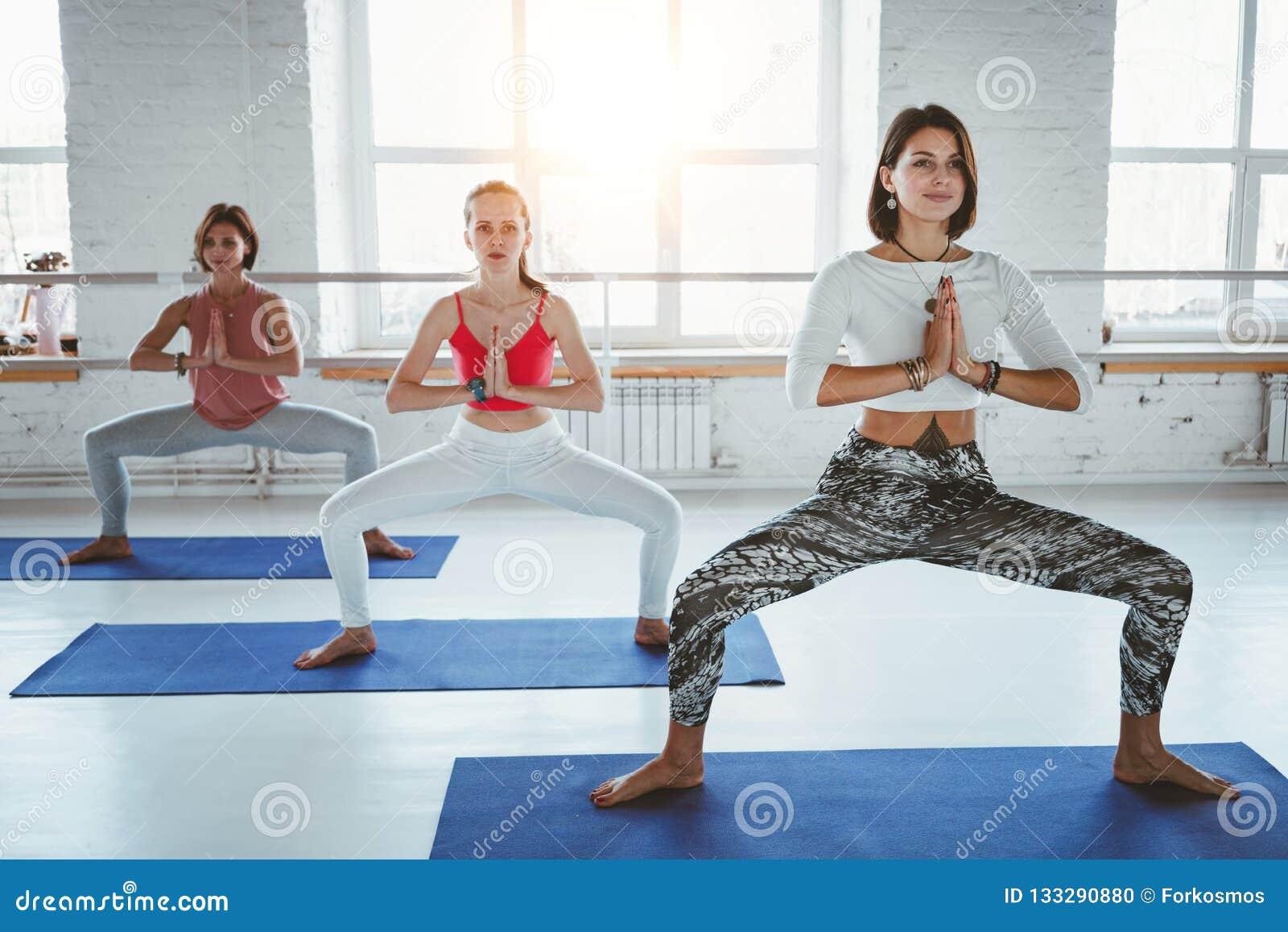 Mujeres adultas aptas que practican actitudes de la yoga en clase de la aptitud Grupo de hembra fuerte sana que hace ejercicios a