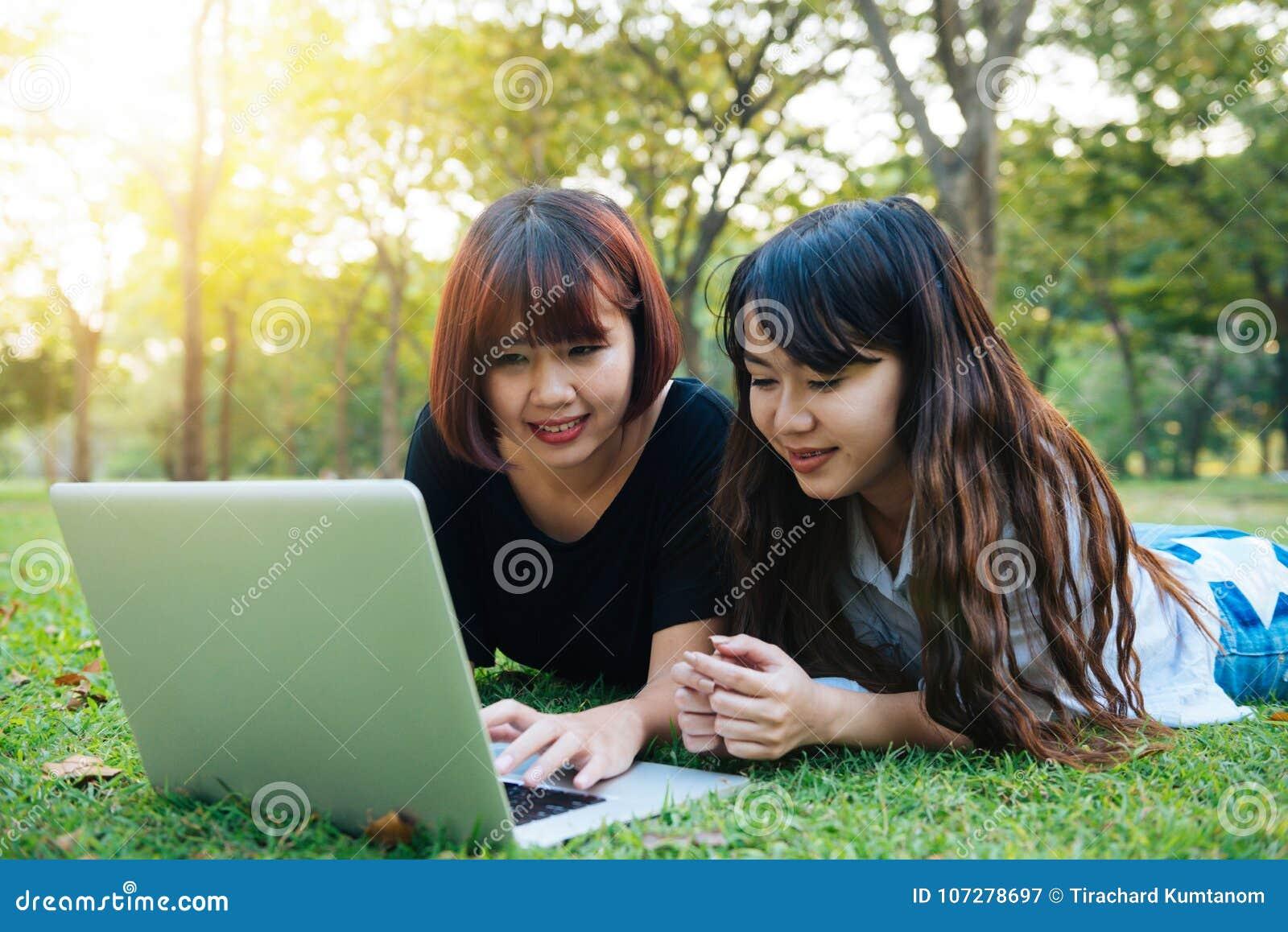 Mujeres asiáticas jovenes del inconformista feliz que trabajan en el ordenador portátil en parque El estudiar en la hierba