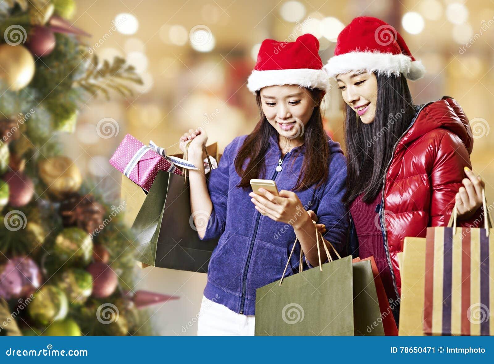 Mujeres asiáticas jovenes que usan el teléfono móvil durante compras de la Navidad