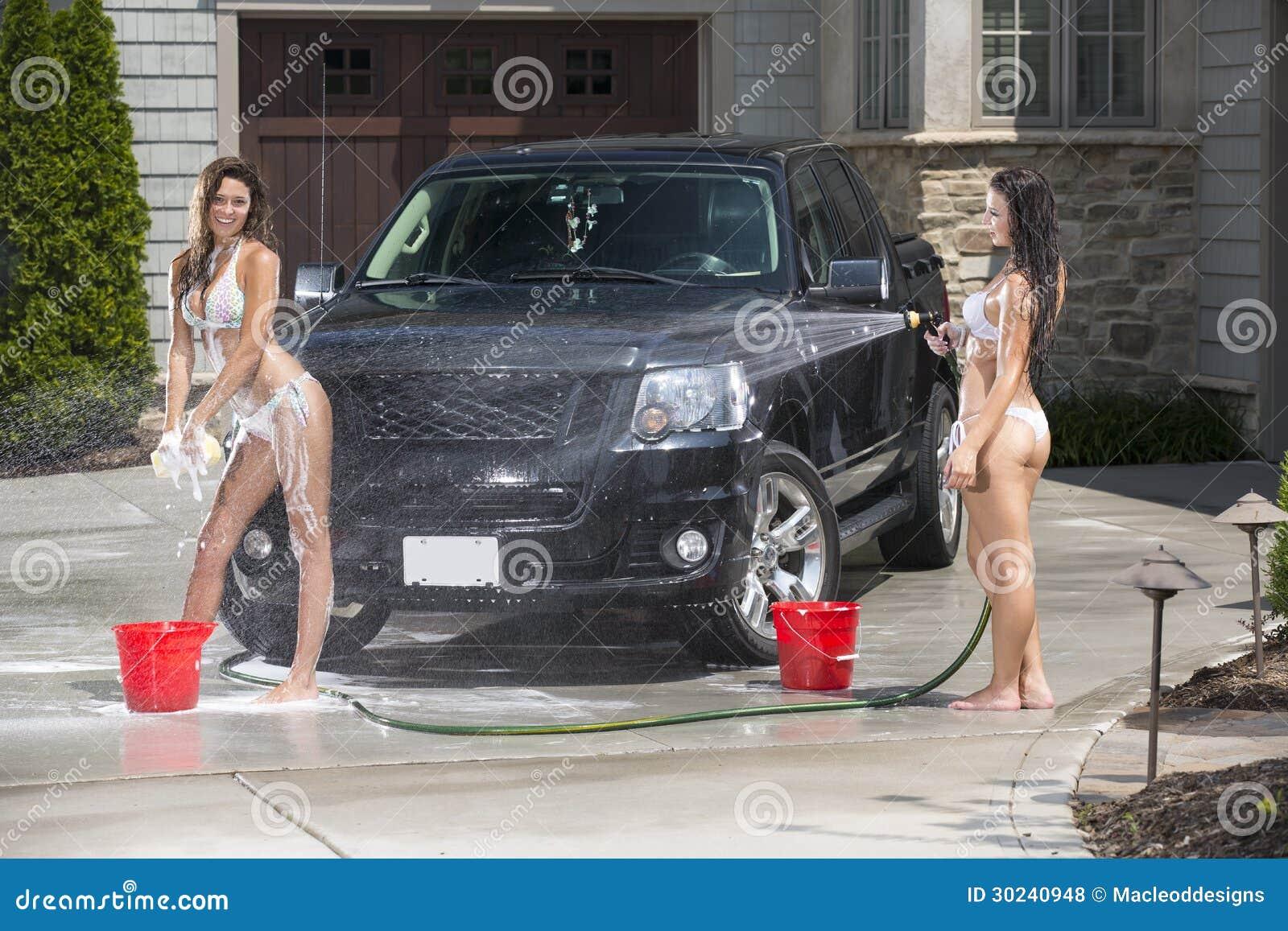 Las muchachas atractivas lavan un camión negro en bikinis