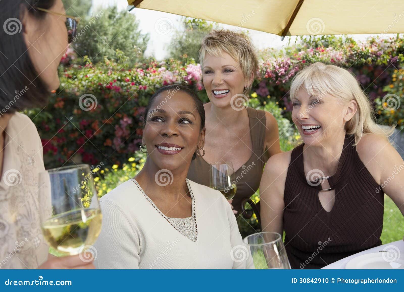 Mujeres con las copas de vino que charlan en la fiesta de jardín