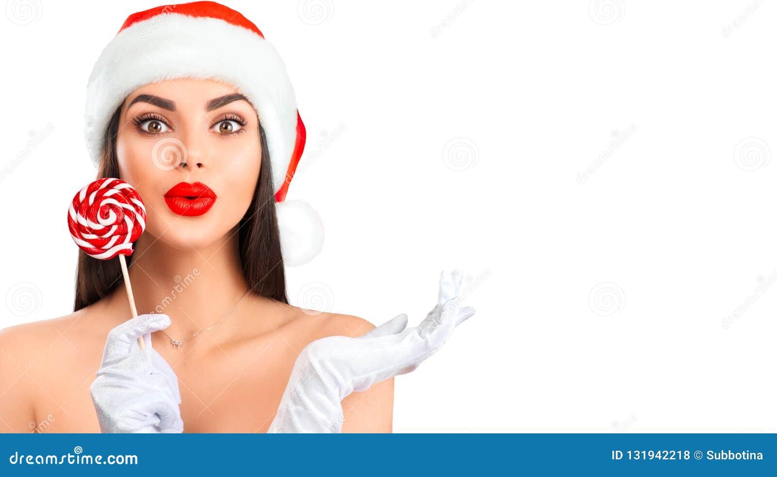 Mujeres de Santa con los bolsos Muchacha modelo alegre en el sombrero de Papá Noel con el caramelo de la piruleta que señala la m