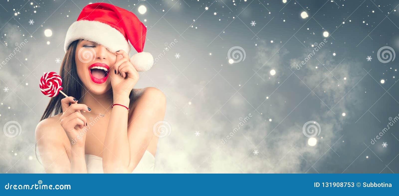 Mujeres de Santa con los bolsos Muchacha modelo alegre en el sombrero de Papá Noel con los labios y el caramelo rojos de la pirul