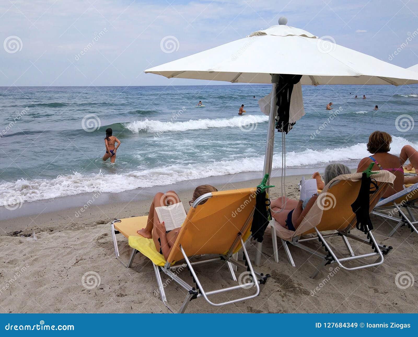 Mujeres debajo de los paraguas que se relajan en sunbeds mientras que otras personas que nadan