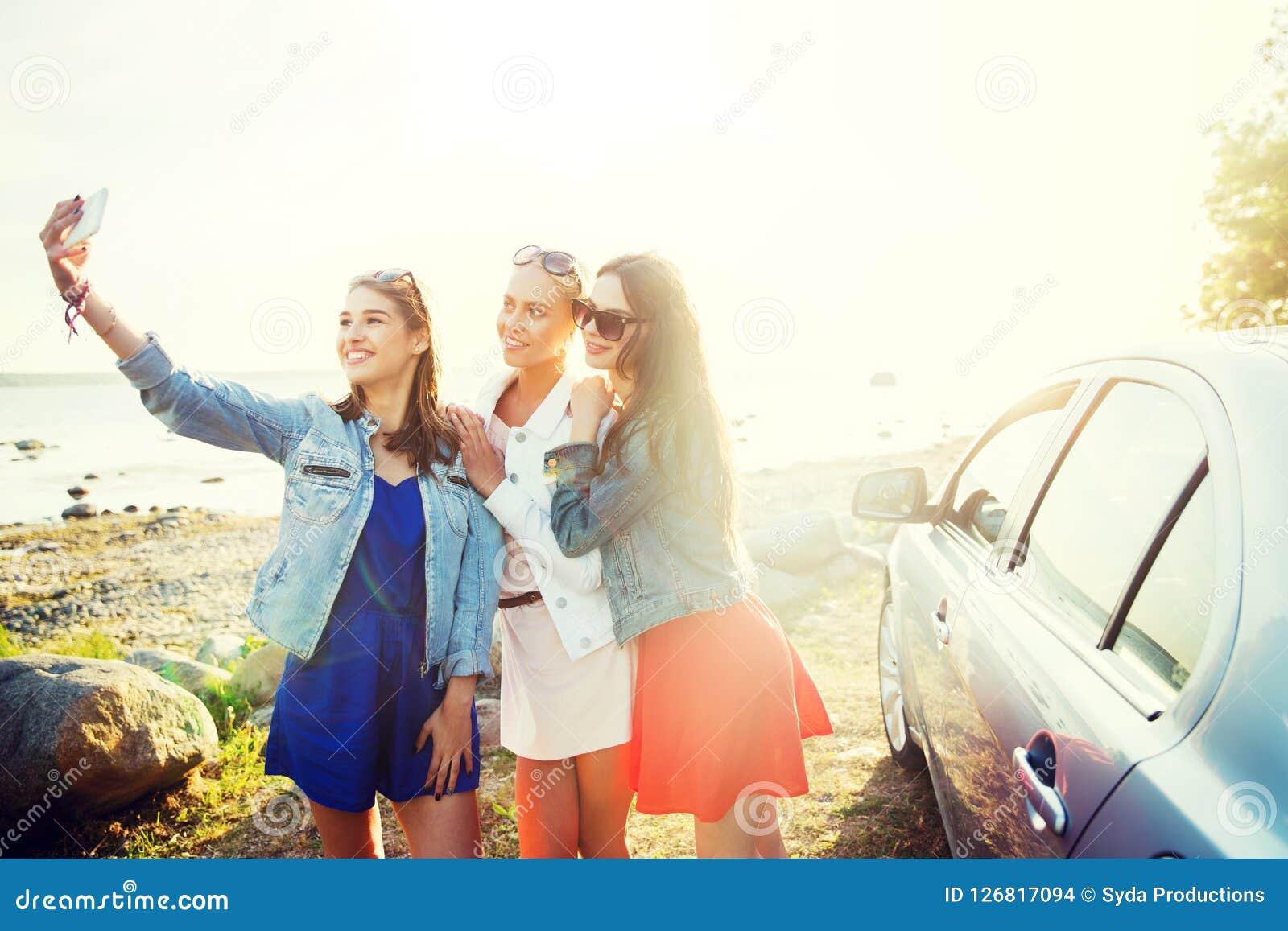 Mujeres felices que toman el selfie cerca del coche en la playa