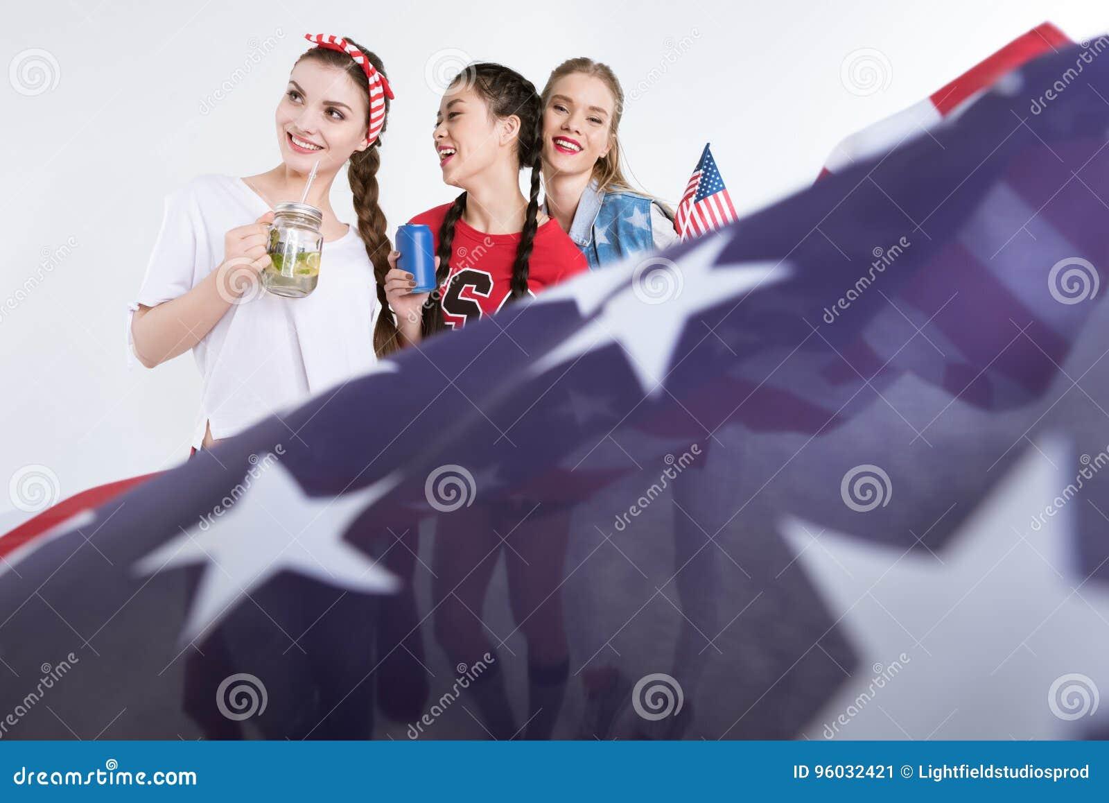 Mujeres jovenes con las bebidas de consumición de la bandera americana aisladas en blanco