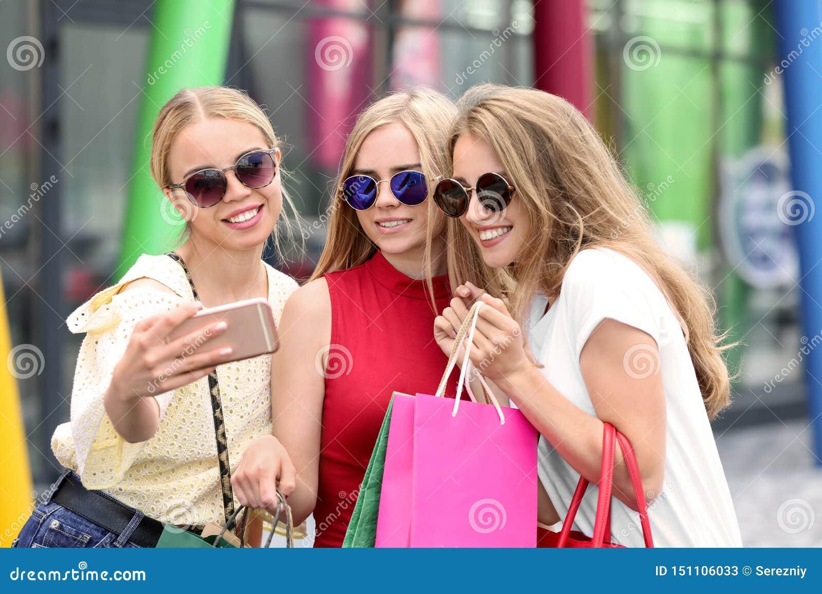 Mujeres jovenes con los bolsos de compras que toman el selfie en la calle de la ciudad