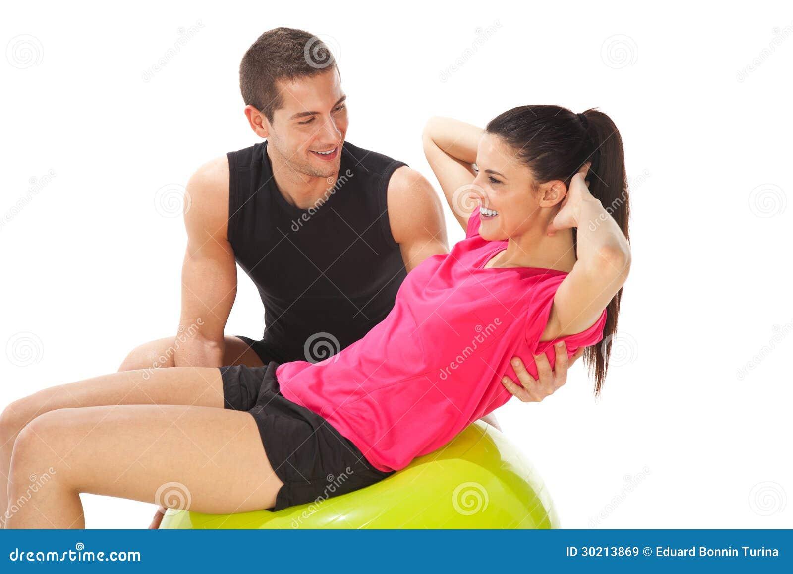 Mujer con su instructor personal que hace ejercicios en bola de la aptitud