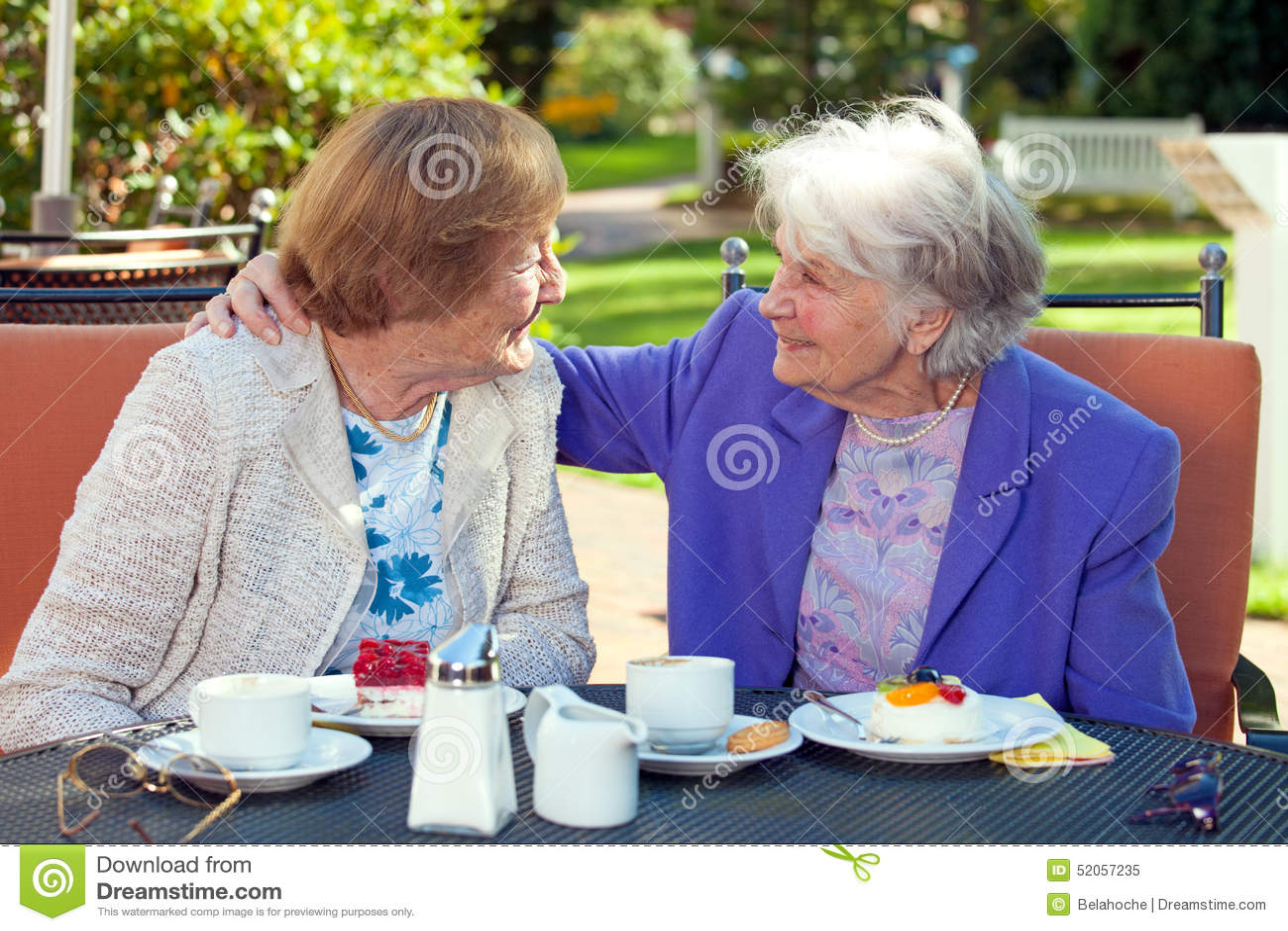 Mujeres mayores alegres que hablan en la tabla al aire libre