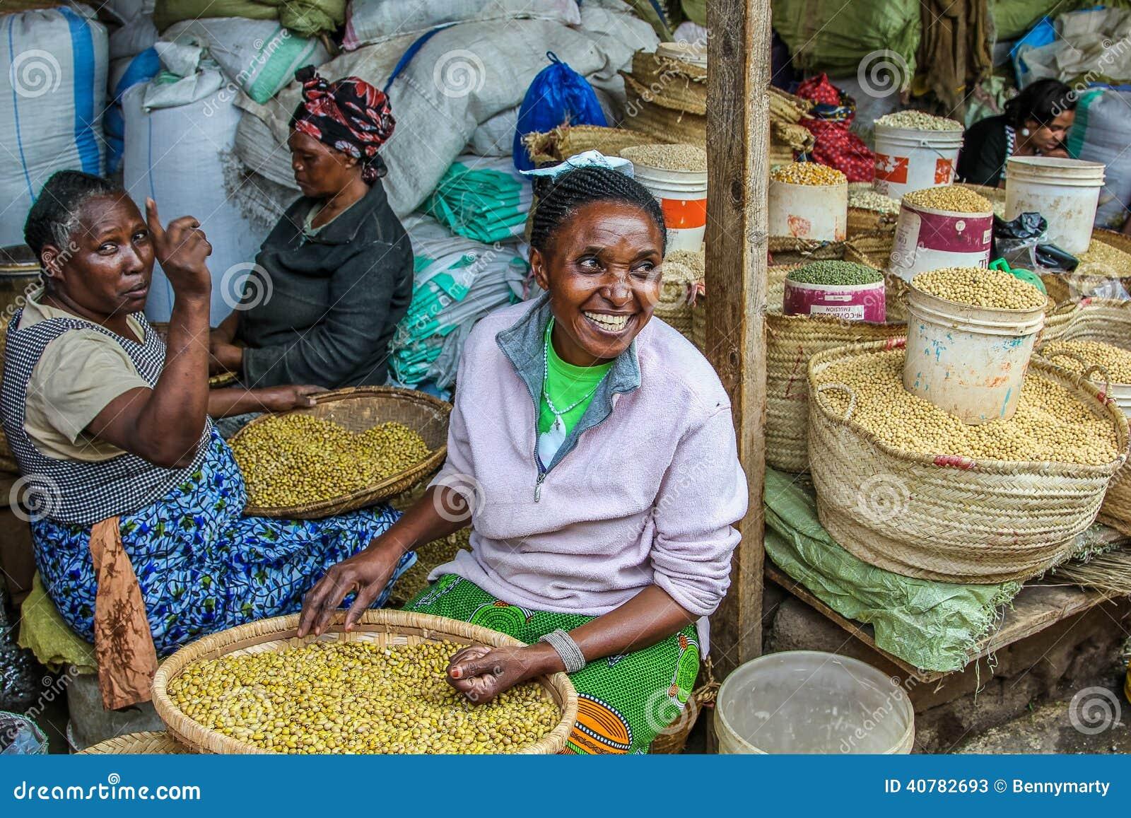 Mujeres mayores sonrientes que venden las especias en su parada