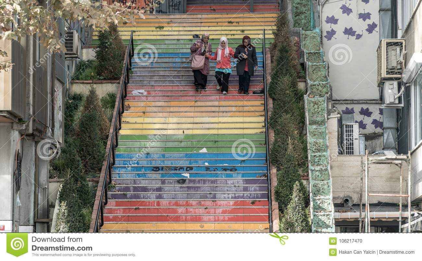 3 mujeres que caminan abajo de las escaleras pintadas en colores del arco iris en Estambul, Turquía