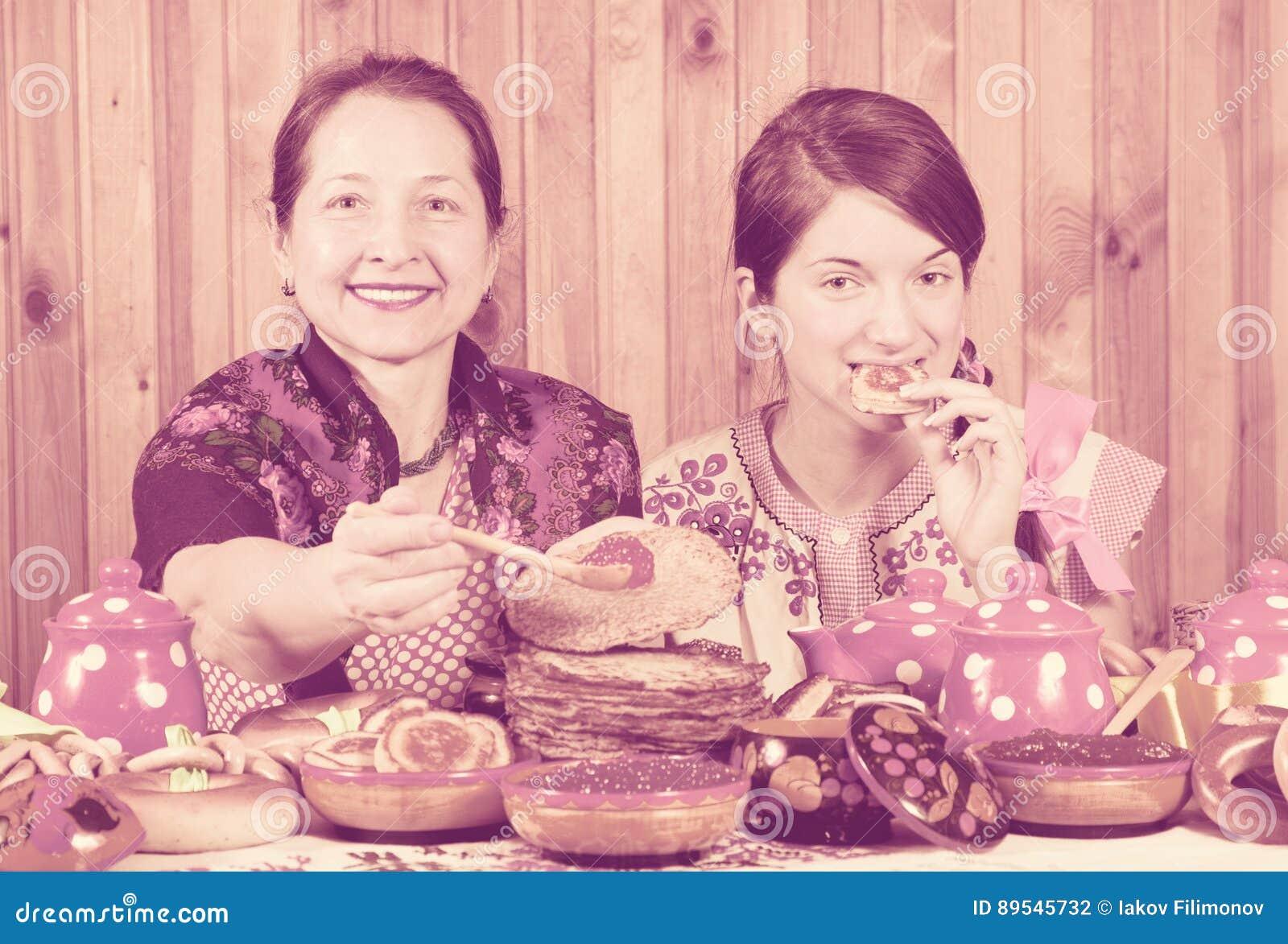 Mujeres que comen la crepe con el caviar durante Shrovetide