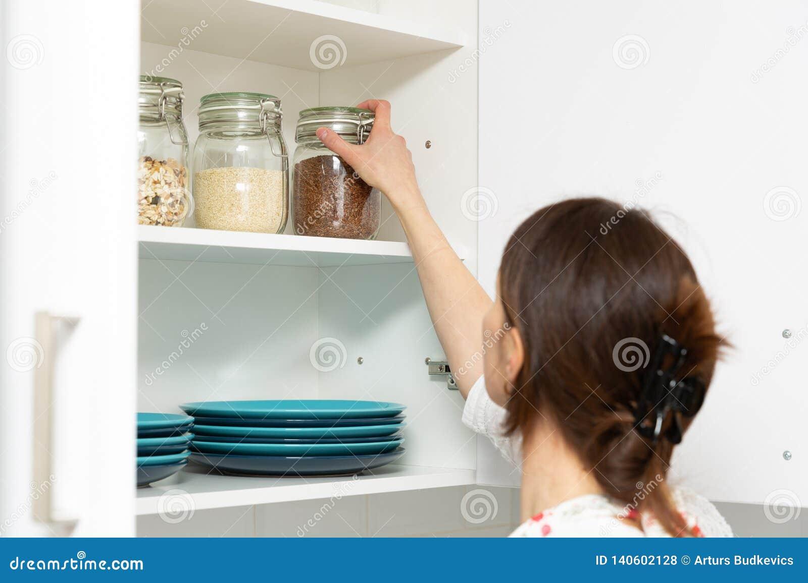 Mujeres que escogen un artículo del aparador del almacenamiento Concepto elegante de la organización de la cocina