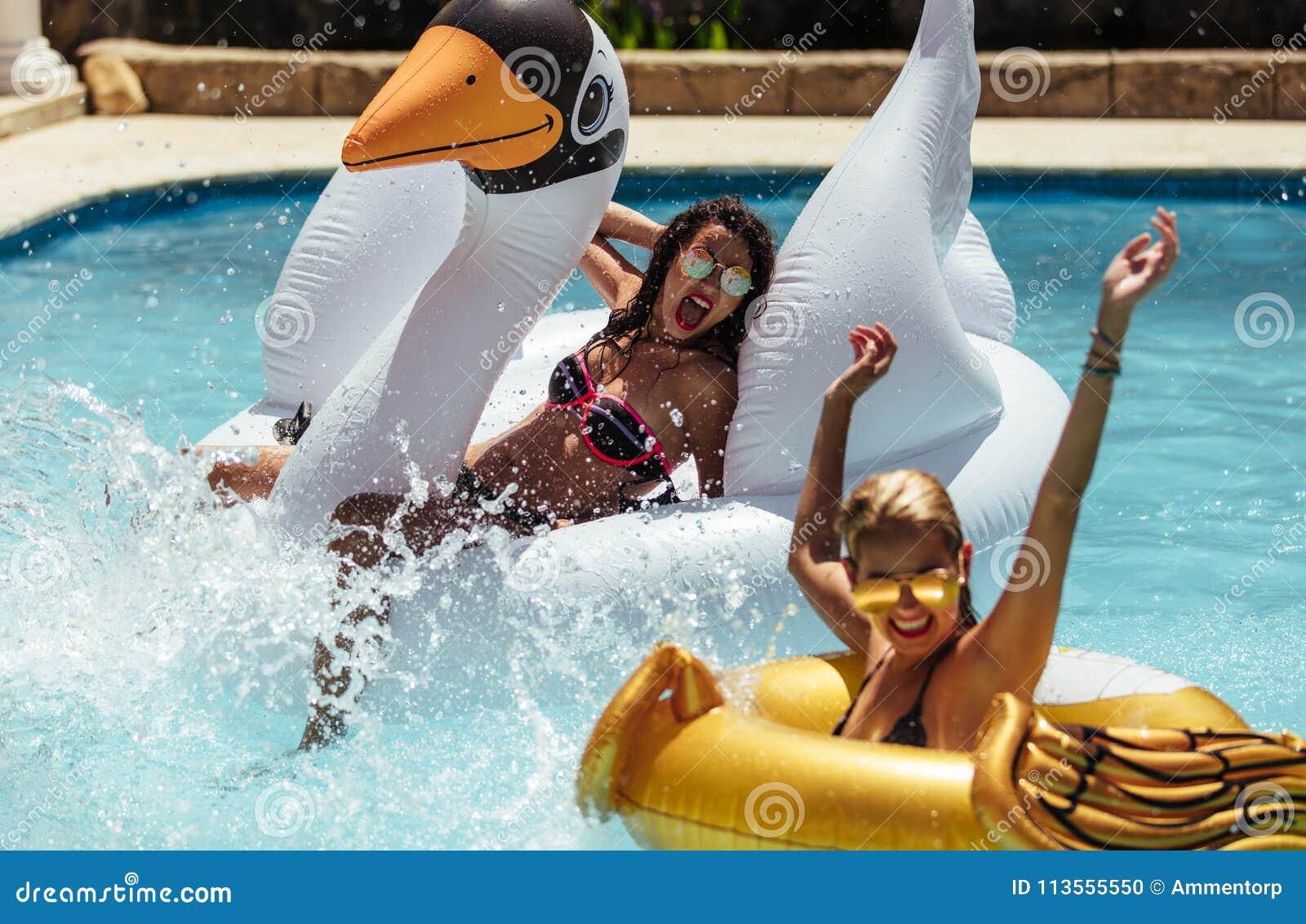 Mujeres que gozan en una piscina en sus vacaciones de verano