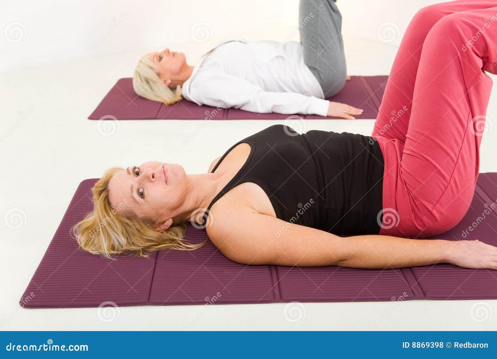 Mujeres que hacen exercices en la estera