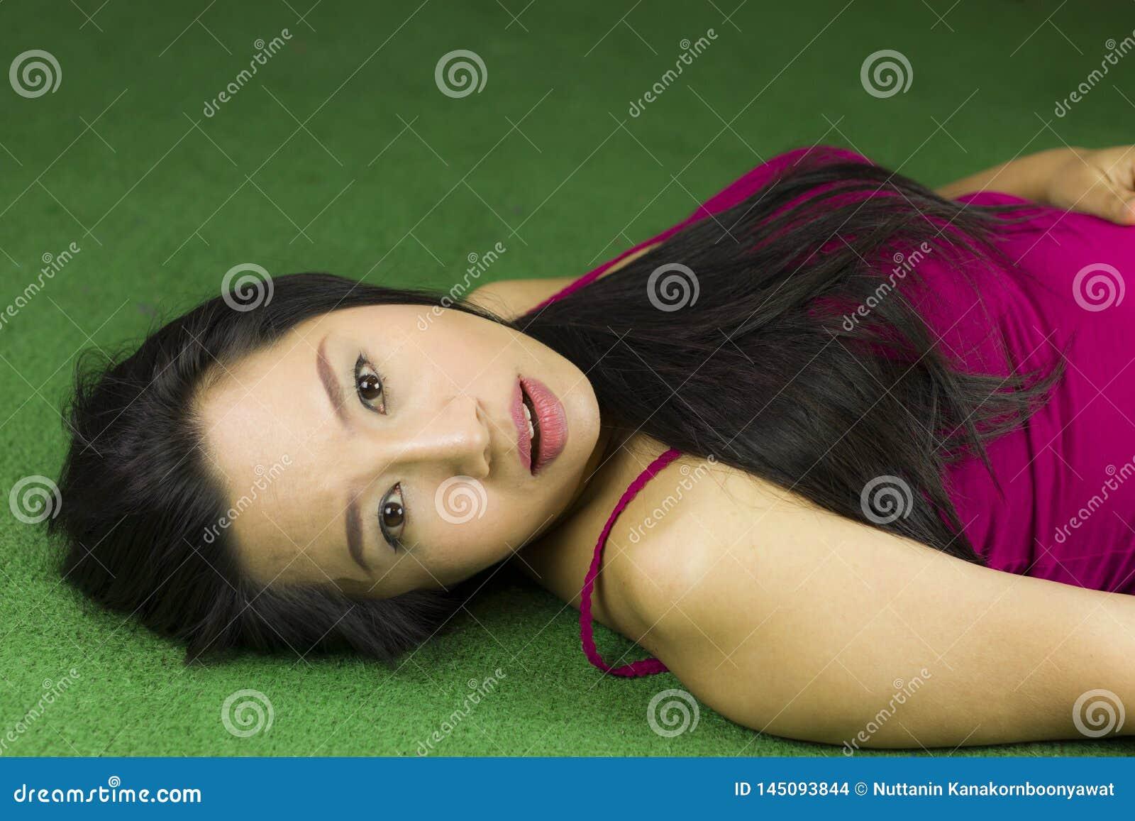 Mujeres que mienten en la hierba verde, una mujer tailandesa hermosa y so?adora colocando en la hierba verde, relaj?ndose mientra
