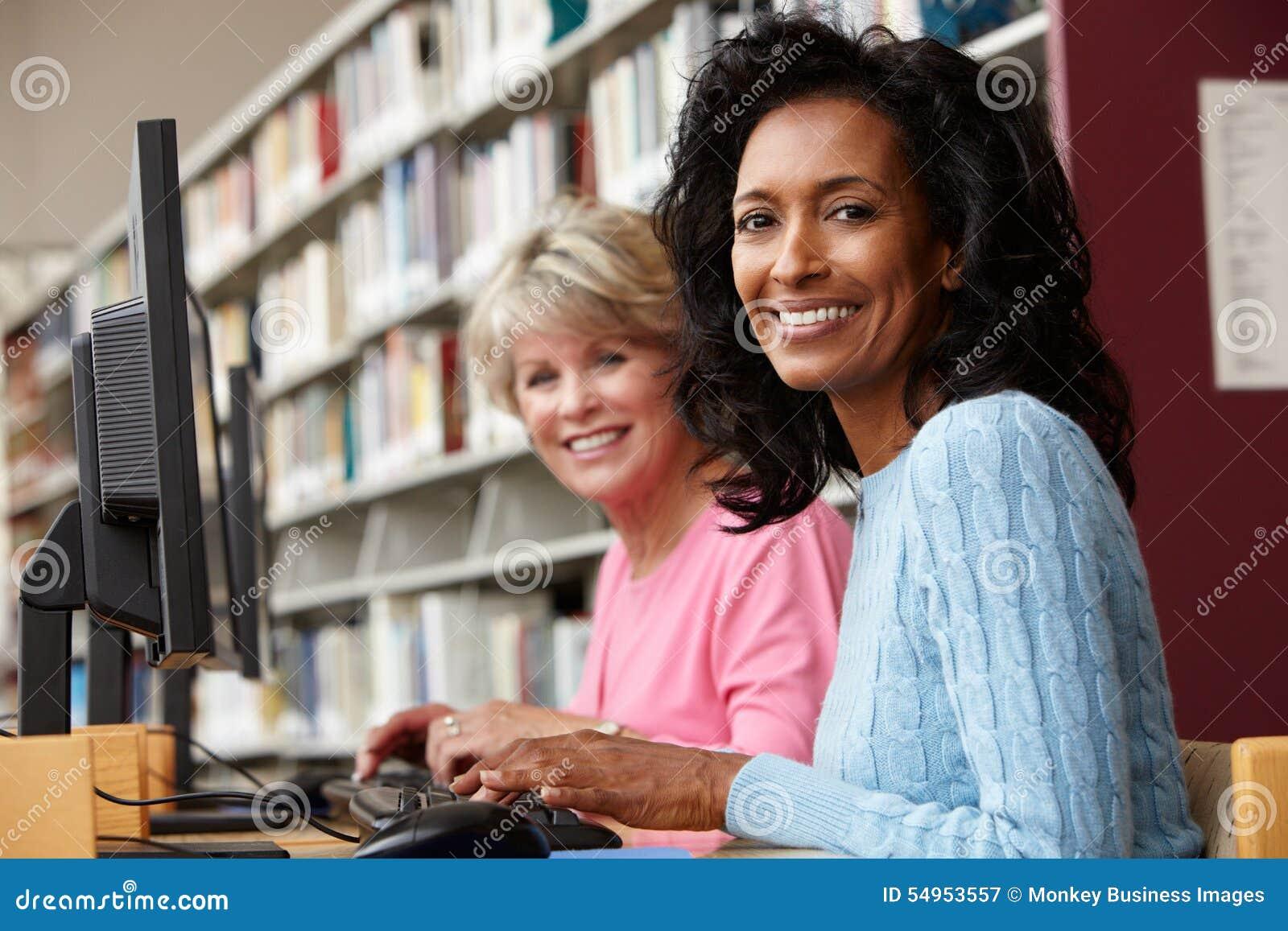 Mujeres que trabajan en los ordenadores en biblioteca