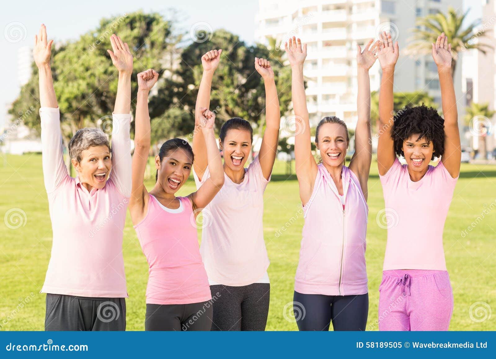 Mujeres sonrientes que llevan el rosa para el cáncer y animar de pecho
