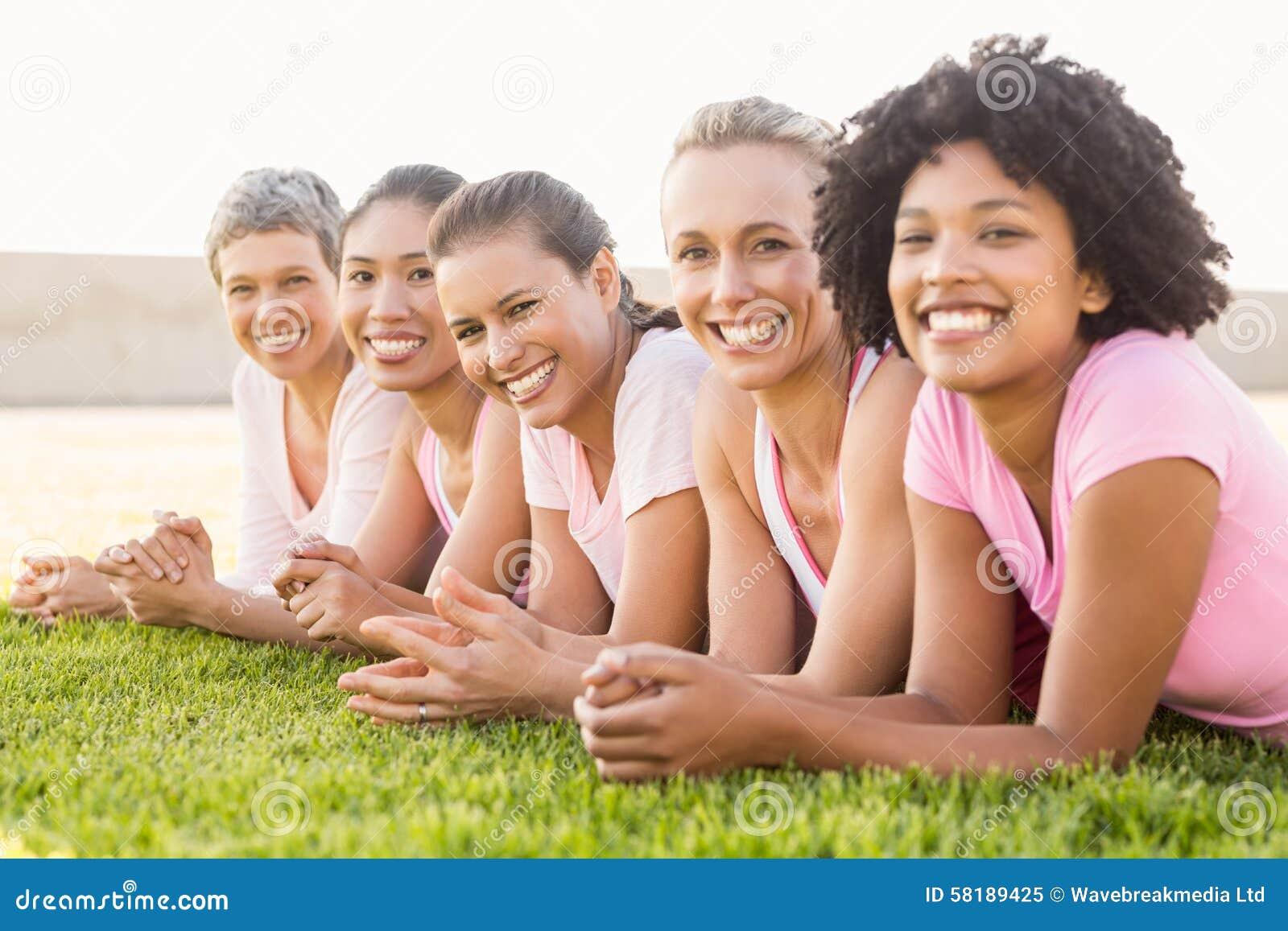 Mujeres sonrientes que mienten en fila y rosa que lleva para el cáncer de pecho