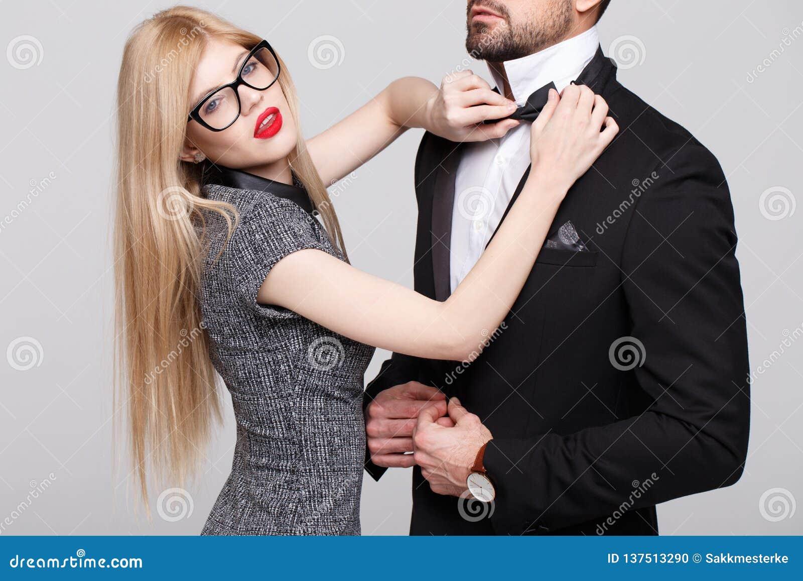 Mulher à moda loura com curva vermelha do laço dos bordos para o homem no smoking