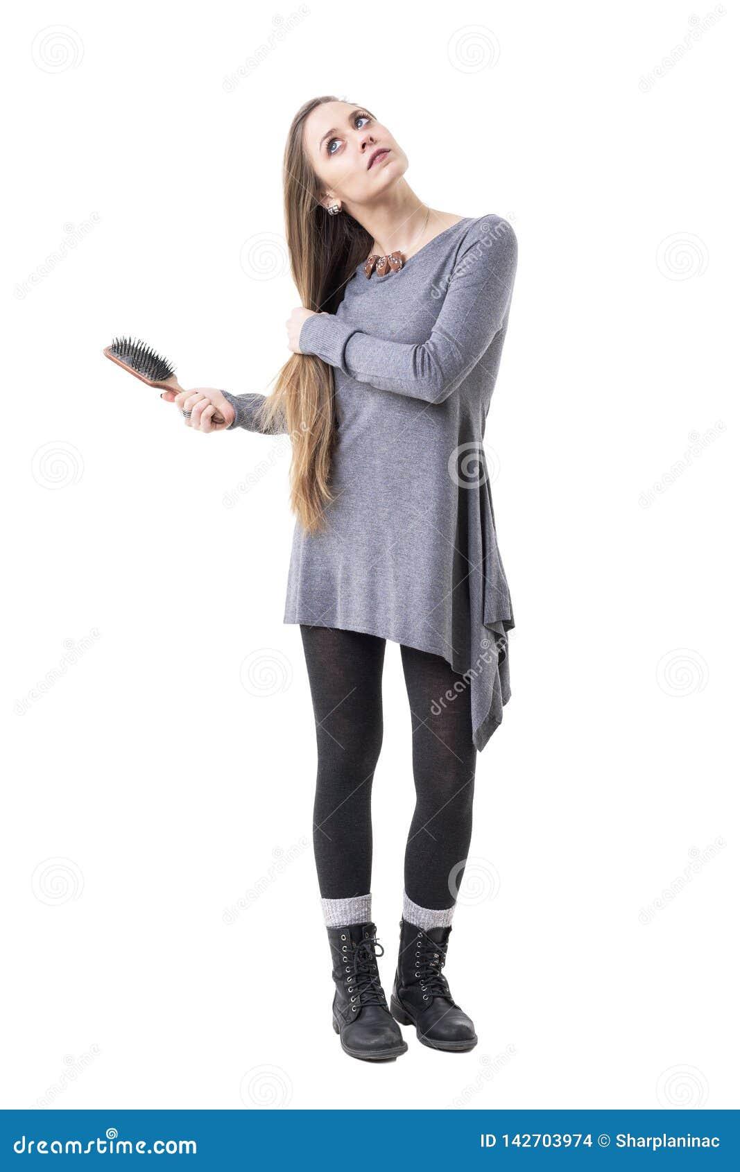 Mulher à moda nova pensativa séria que olha acima e que guarda ao escovar seu cabelo com escova
