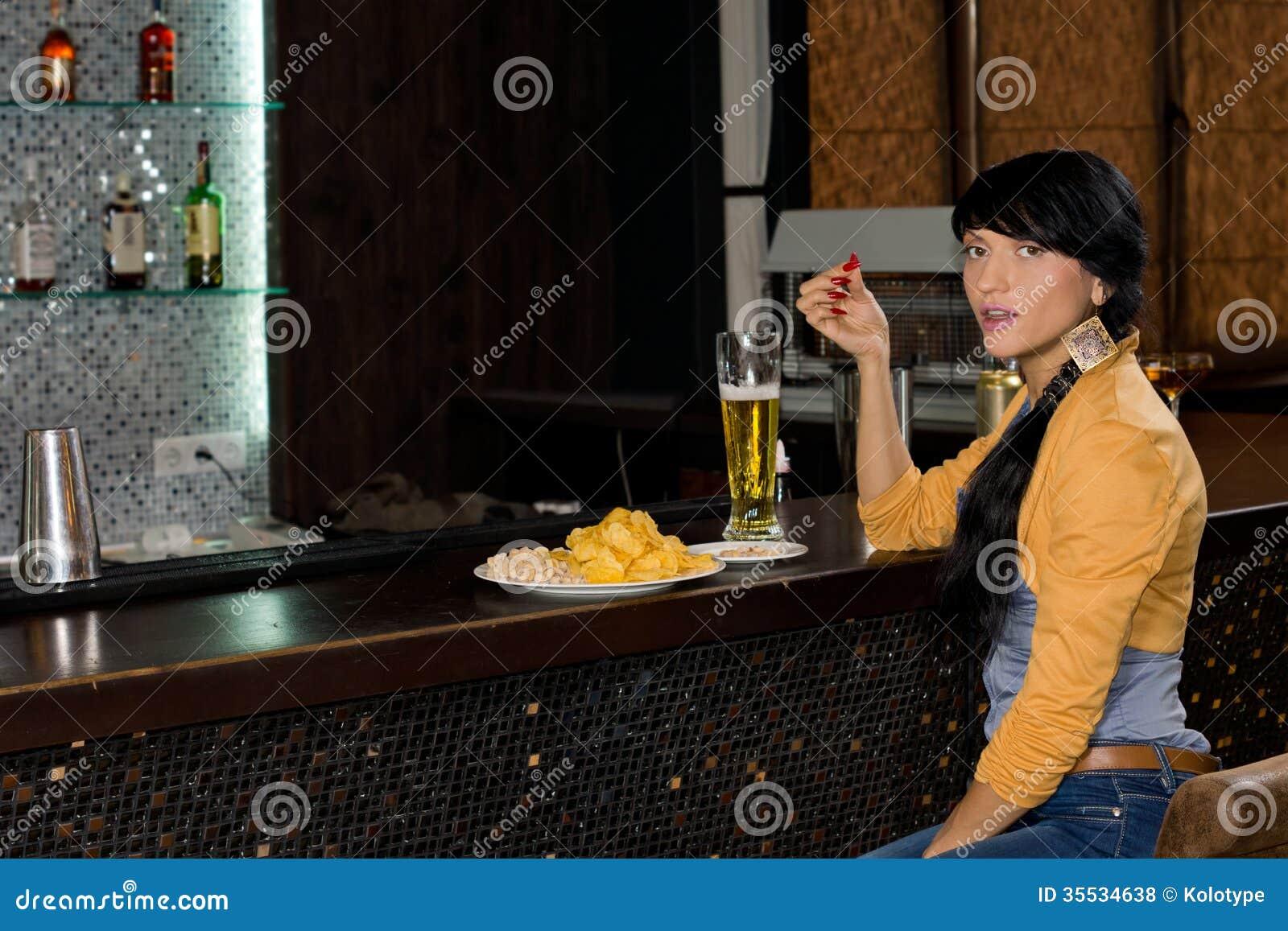 Mulher à moda que bebe apenas no contador da barra