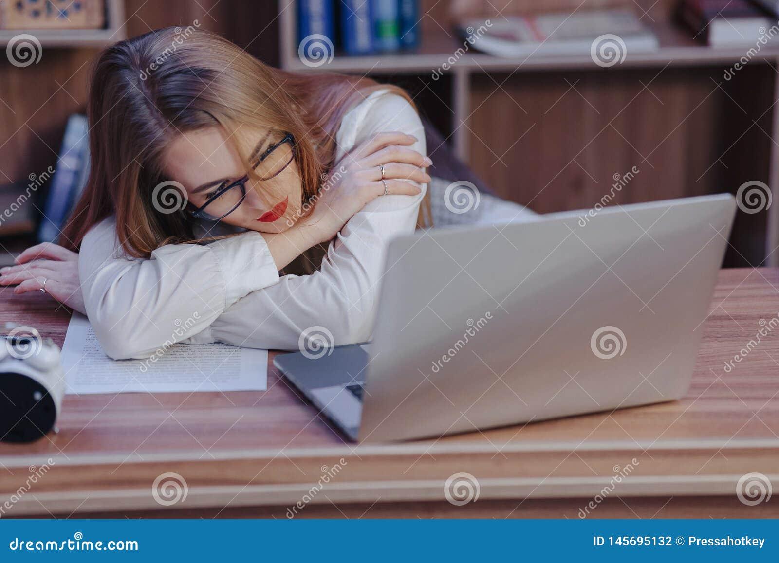 A mulher à moda trabalha em uma mesa do portátil em um escritório moderno