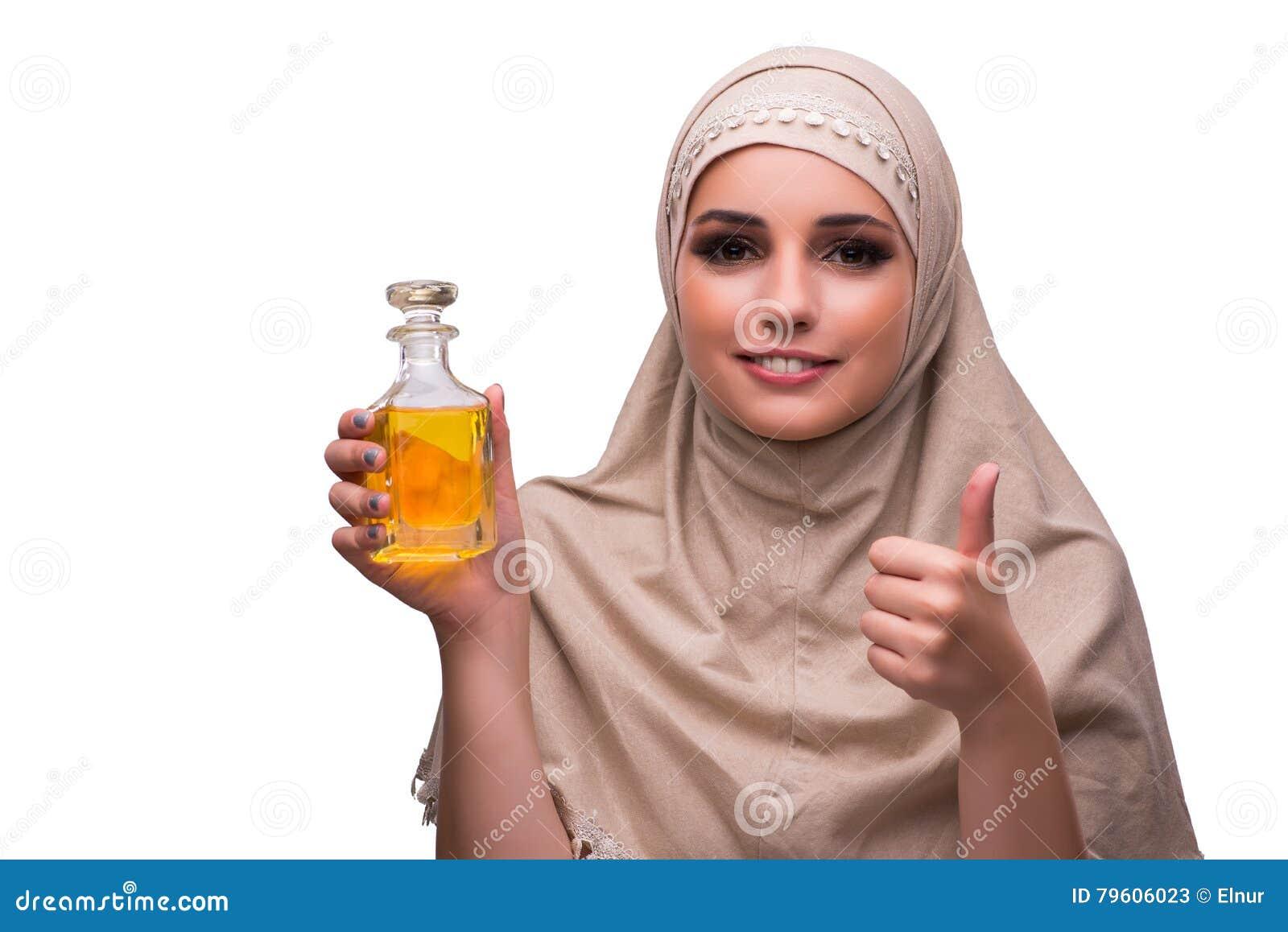 A mulher árabe com a garrafa do perfume isolada no branco