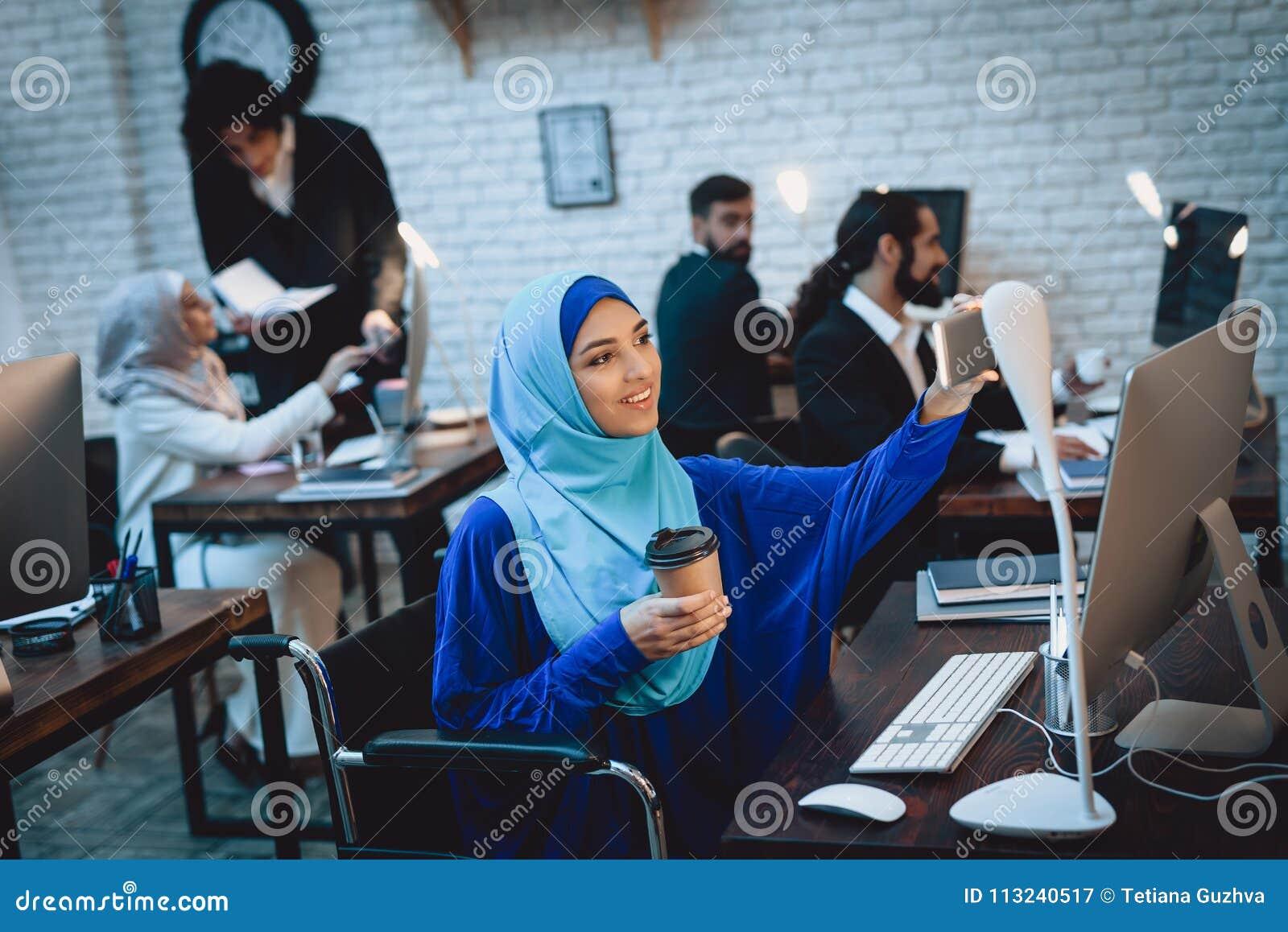 Mulher árabe deficiente na cadeira de rodas que trabalha no escritório A mulher está tomando o selfie