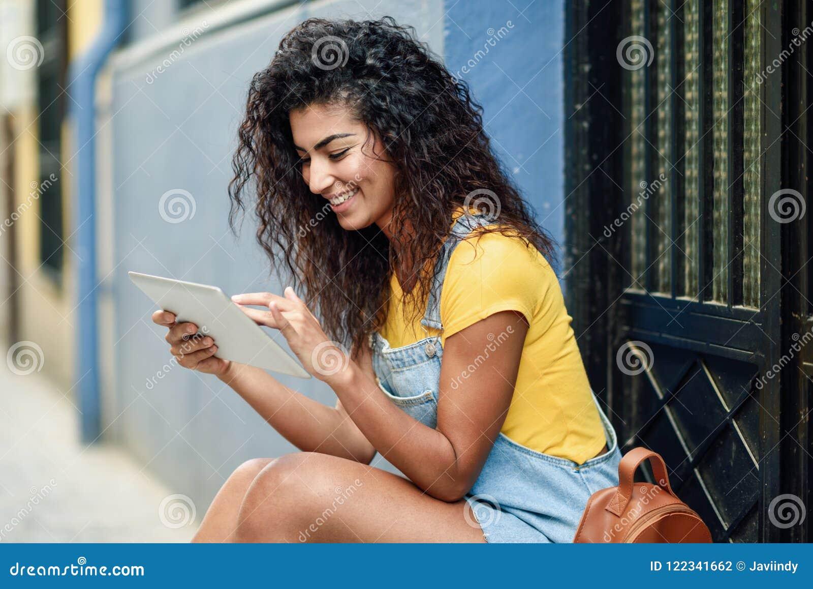 Mulher árabe nova que usa sua tabuleta digital fora