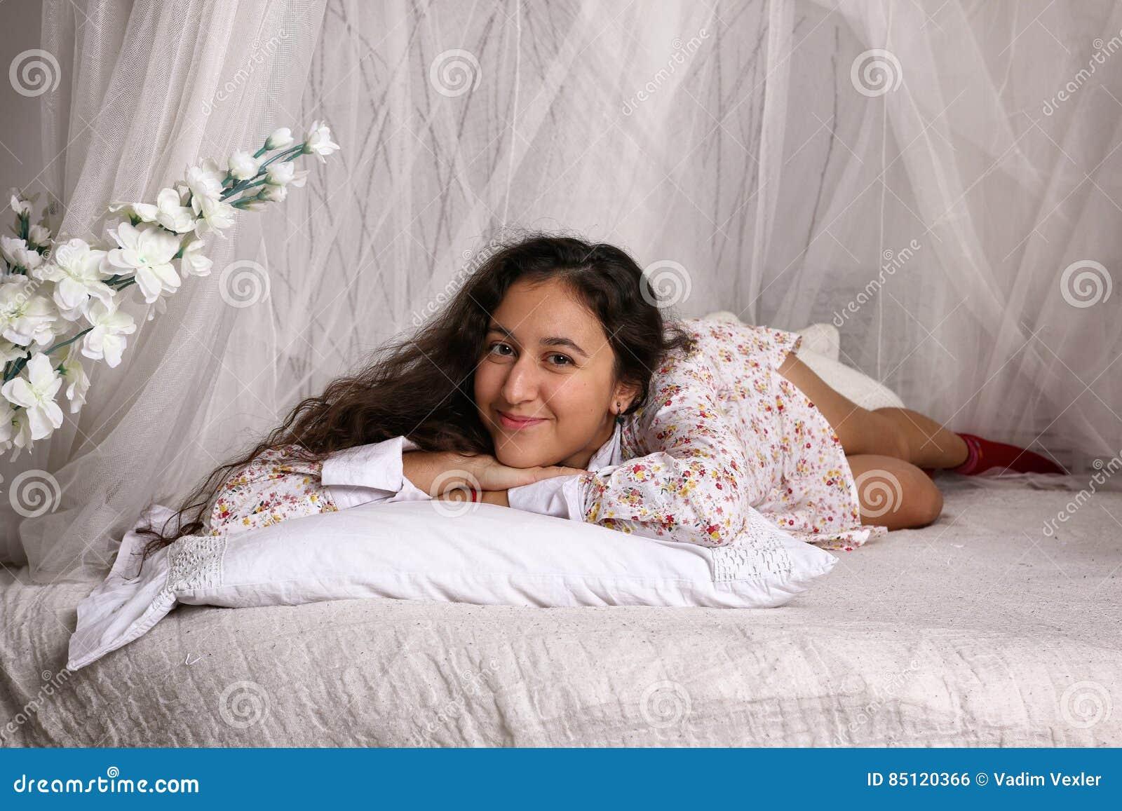A mulher aciganada nova encontra-se em uma cama branca com dossel