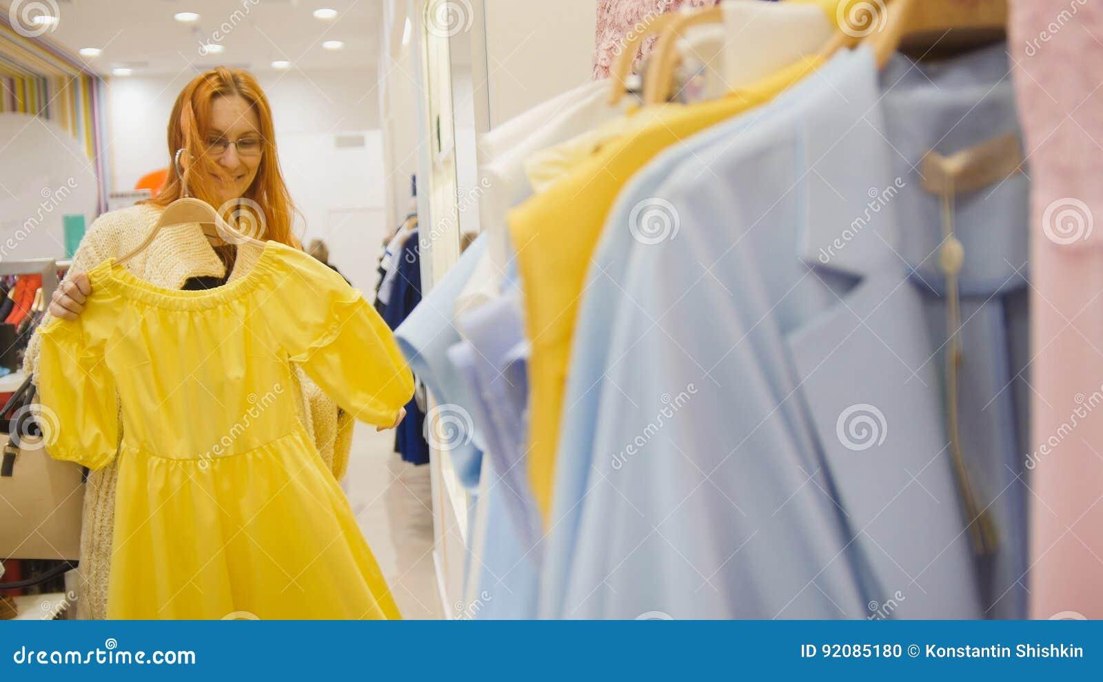 A mulher adorável em uma loja de roupa escolhe um vestido amarelo - conceito da compra