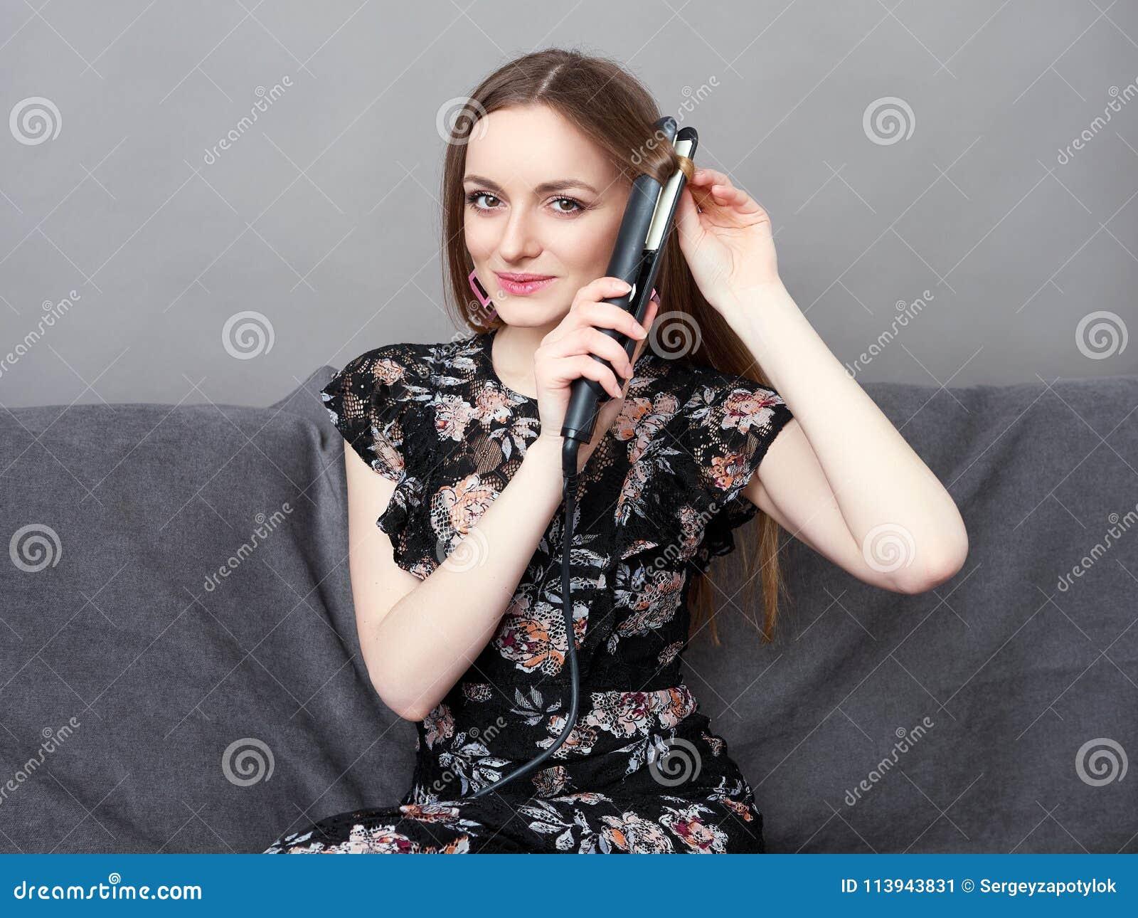 Mulher adorável nova feliz no vestido longo no sofá cinzento que mantém o styler do cabelo em casa contra a parede cinzenta