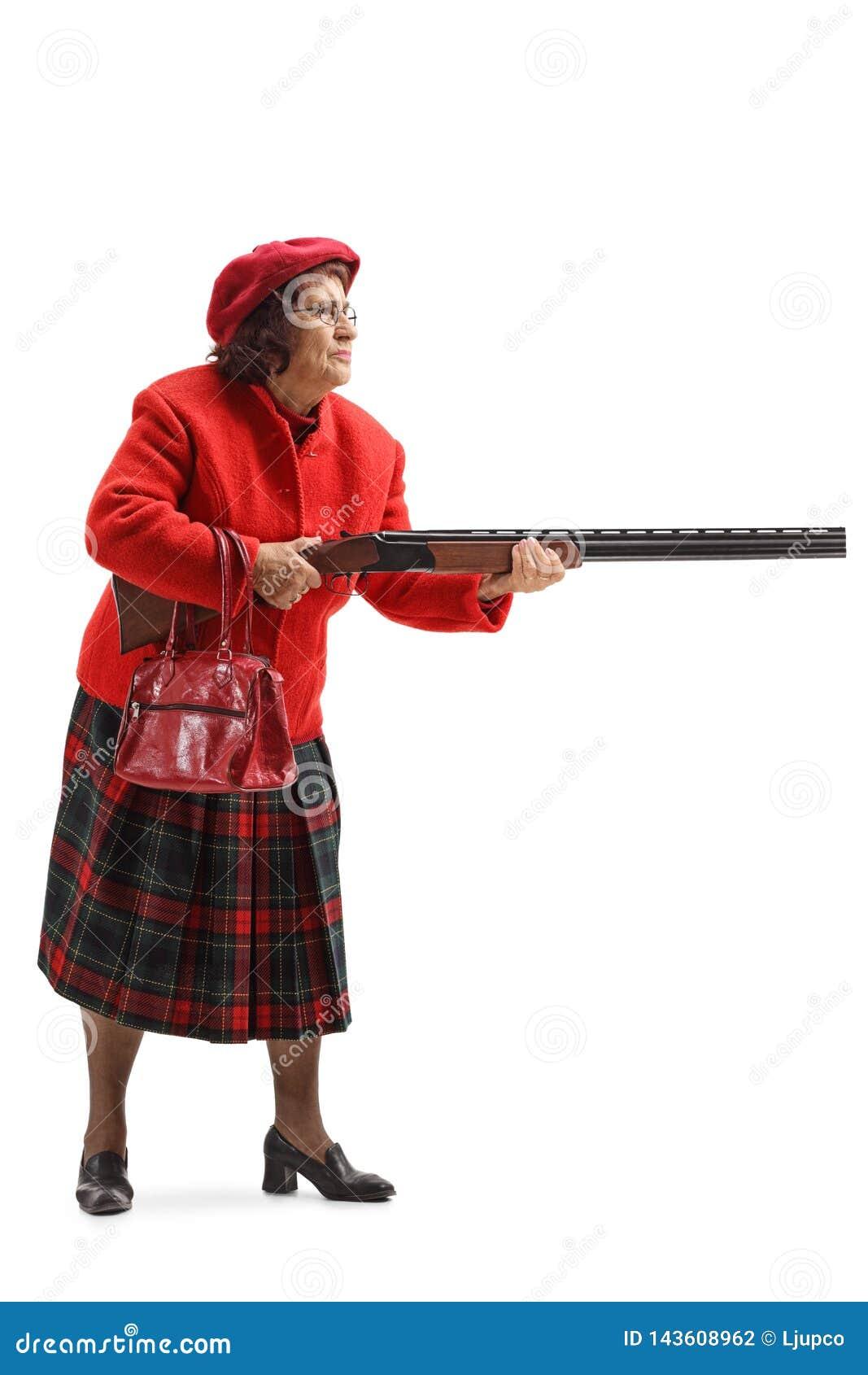 Mulher adulta em um revestimento vermelho que guarda uma espingarda