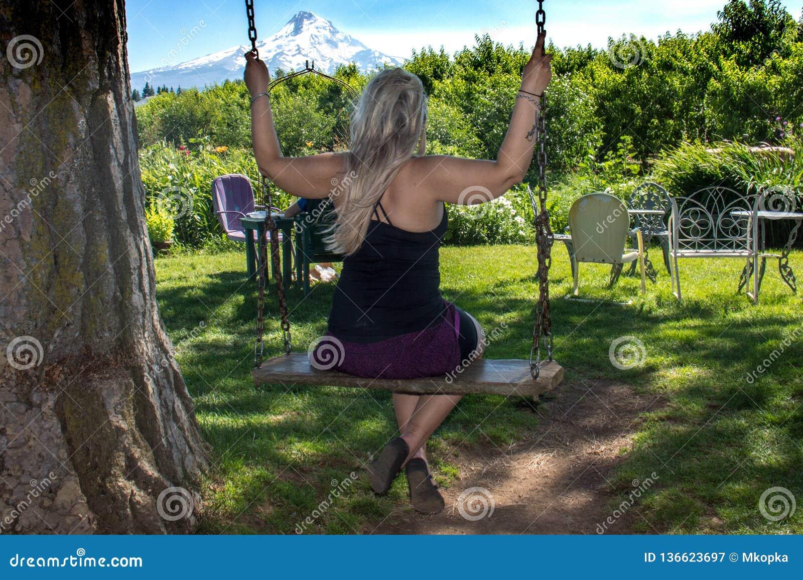 Mulher adulta que balança em um balanço de madeira da árvore no Mt Capa Oregon Conceito para a felicidade, infantil, inocência, d