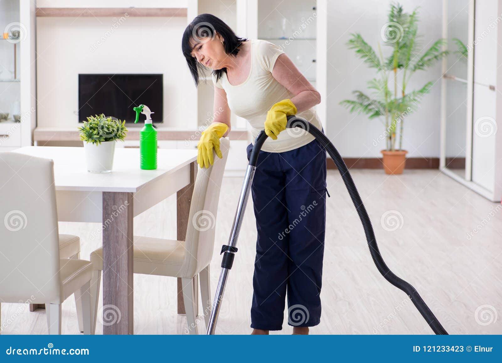 A mulher adulta superior cansado após a casa da limpeza do vácuo