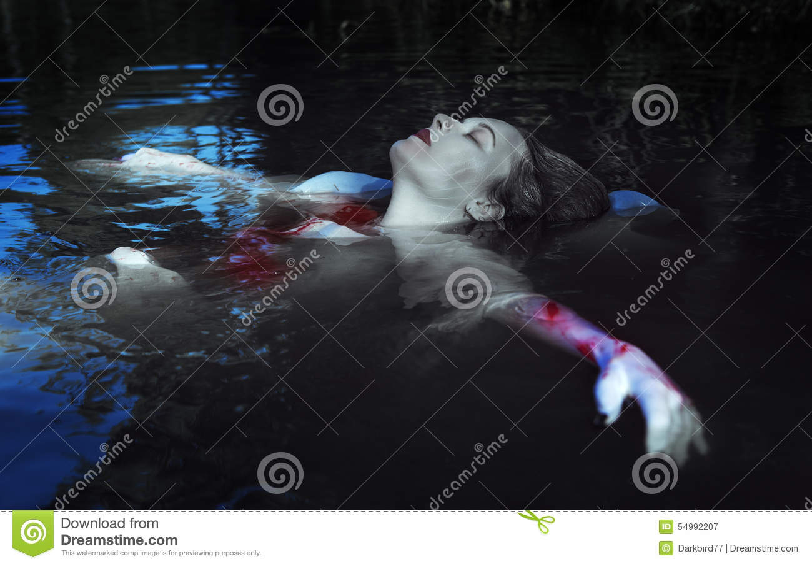 Mulher afogada bonita no vestido ensanguentado que encontra-se na água