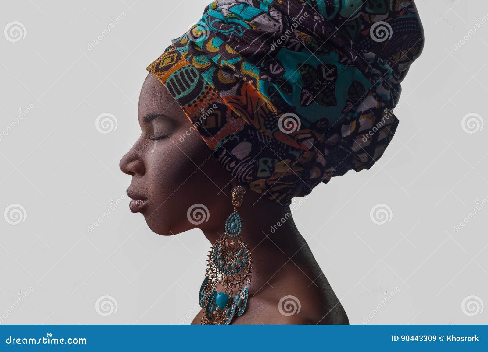 Mulher africana bonita nova no estilo tradicional com lenço, brincos gritando, isolada no fundo cinzento