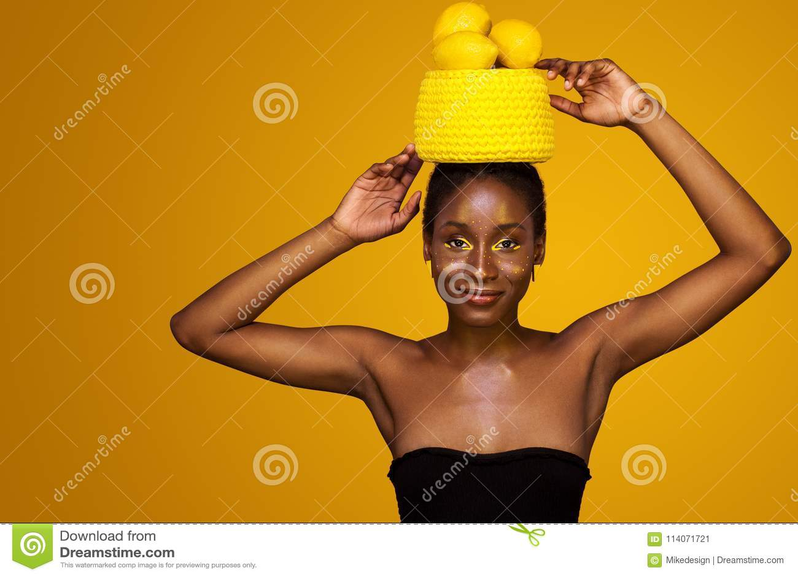 Mulher africana nova alegre com composição amarela em seus olhos Modelo fêmea contra o fundo amarelo com limões amarelos