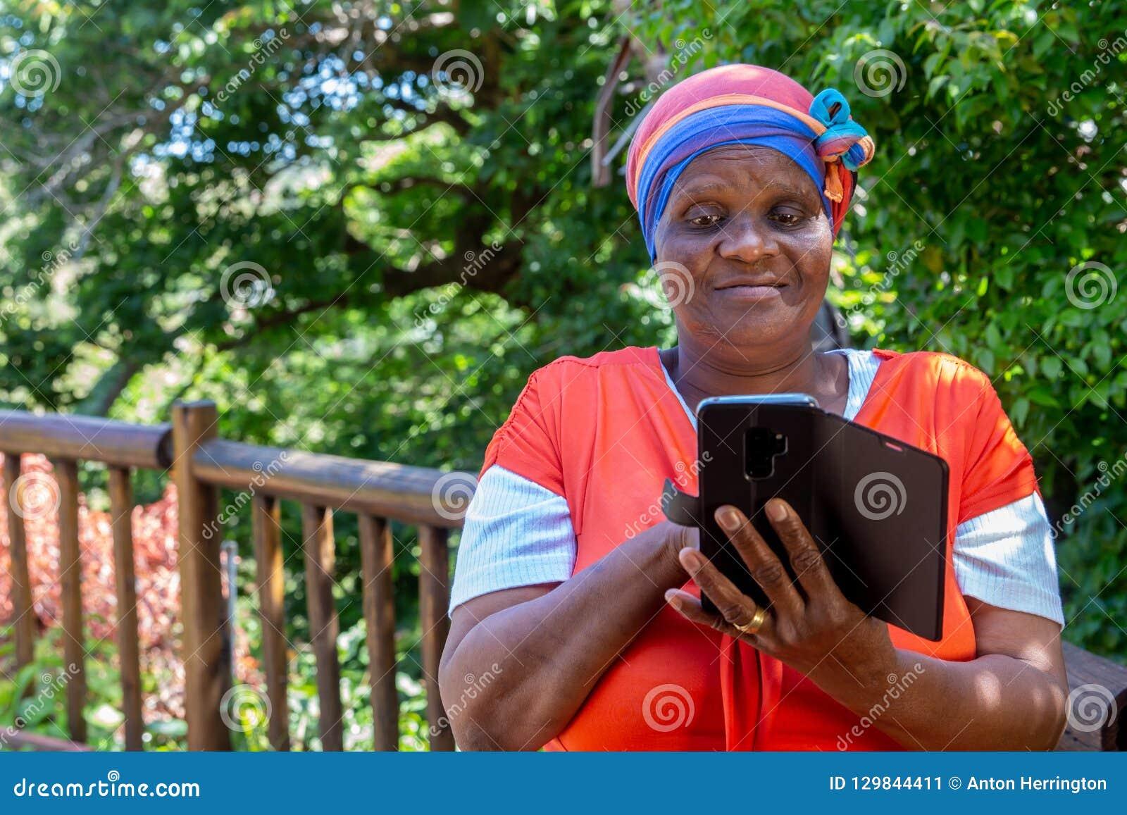 Mulher africana que olha seu telefone celular