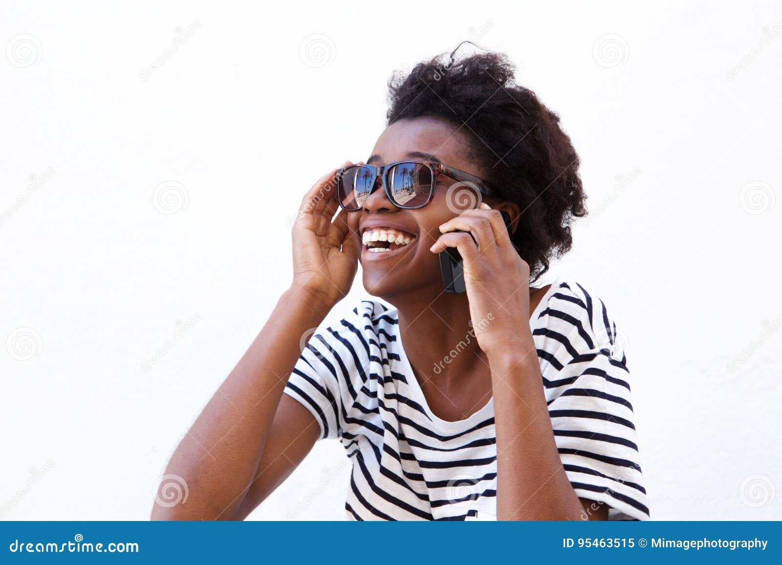 Mulher afro-americana nova de riso com telefone celular
