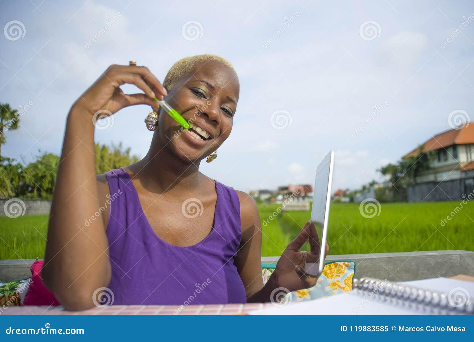 Mulher afro-americana preta bem sucedida atrativa e feliz nova que trabalha com a almofada digital da tabuleta fora no smili verd