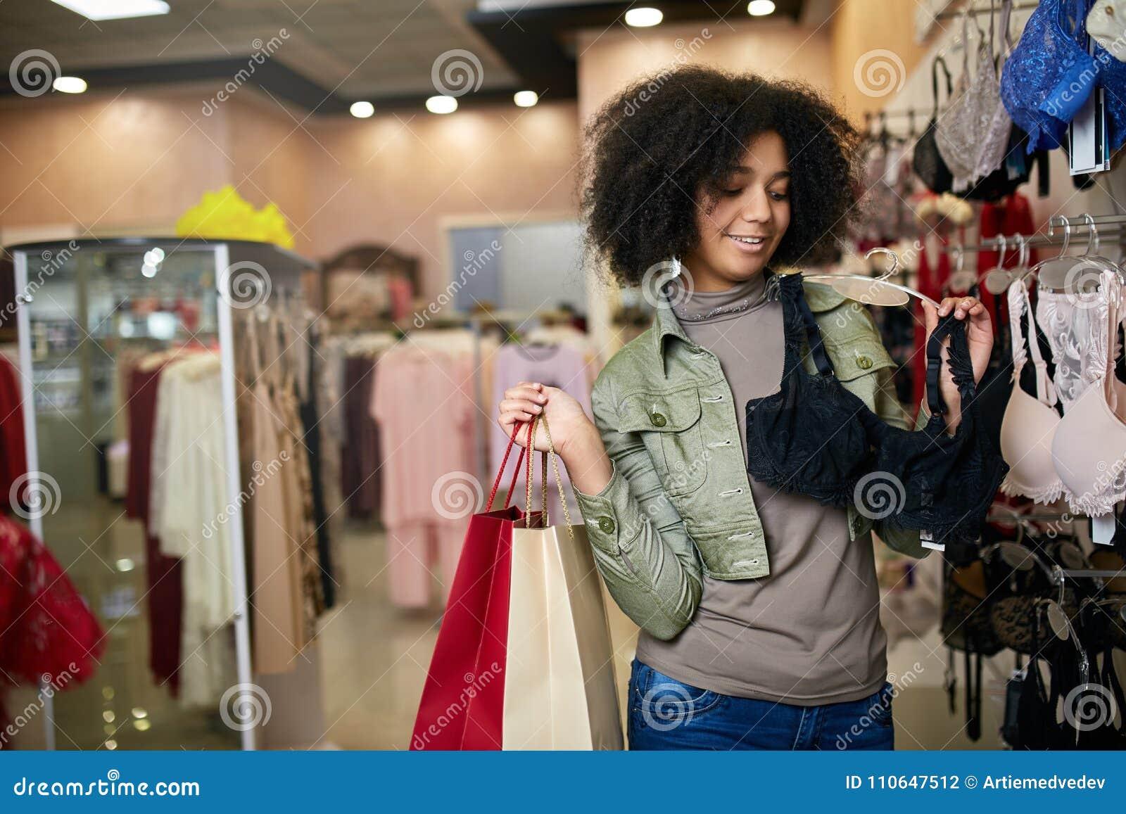 Mulher afro-americano atrativa de sorriso dos jovens que escolhe o tamanho direito do sutiã no boutique da loja da roupa interior