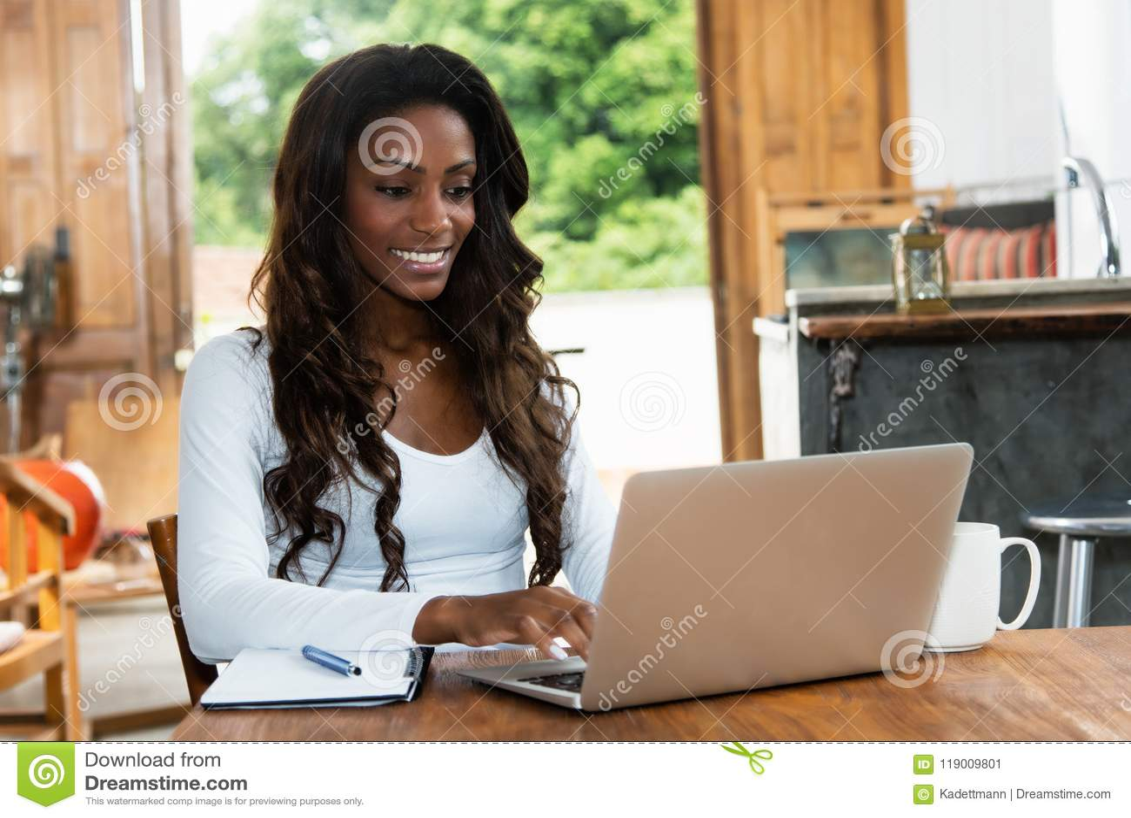 Mulher afro-americano com o cabelo longo que trabalha no computador