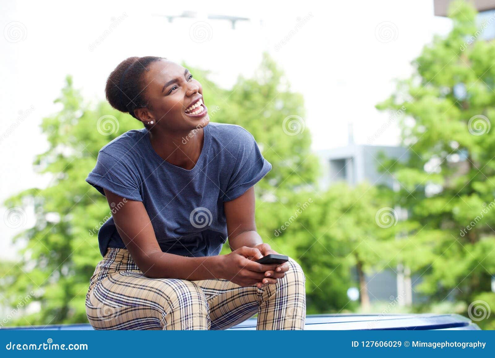 Mulher afro-americano nova bonita que ri com telefone celular fora