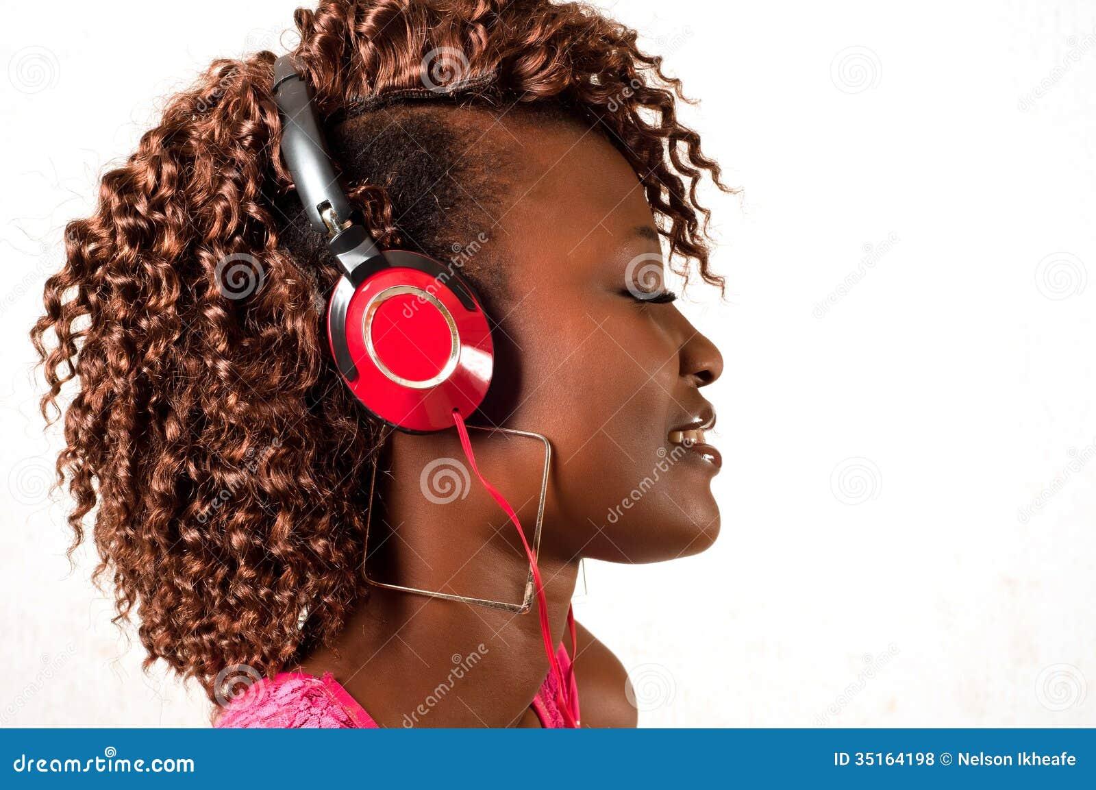 Mulher afro-americano nova que escuta a música
