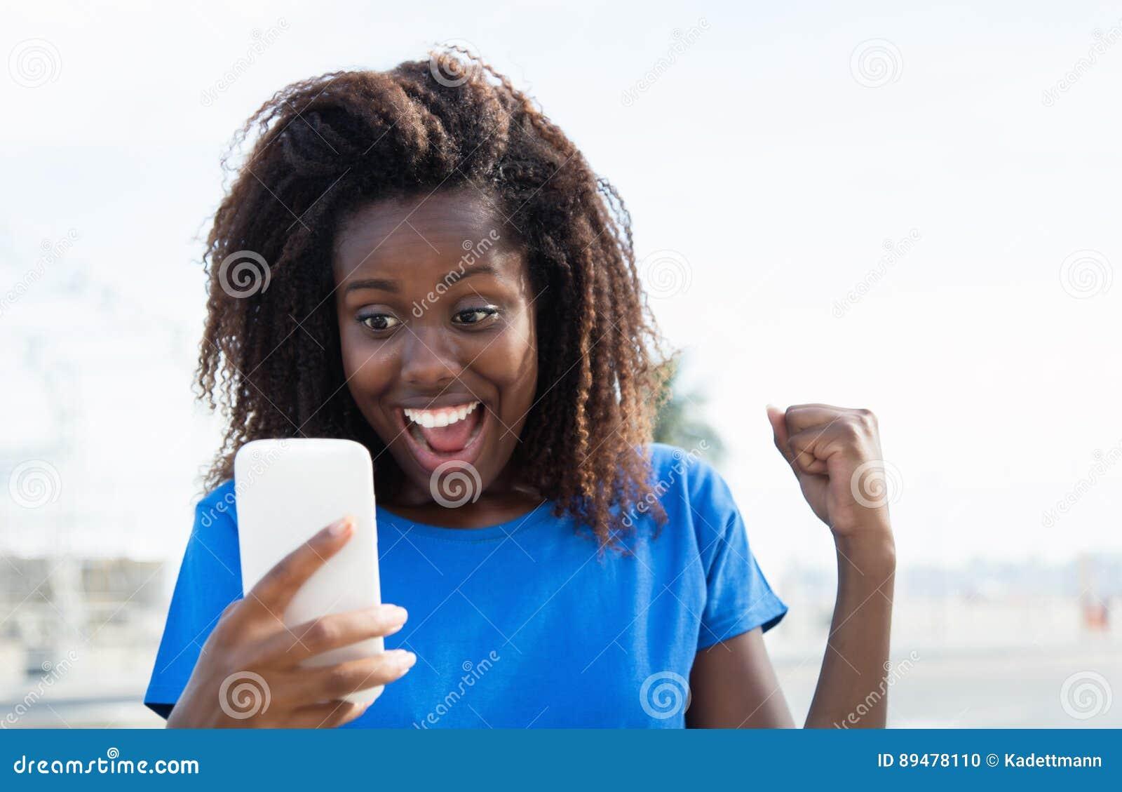 Mulher afro-americano que recebe a boa notícia pelo telefone