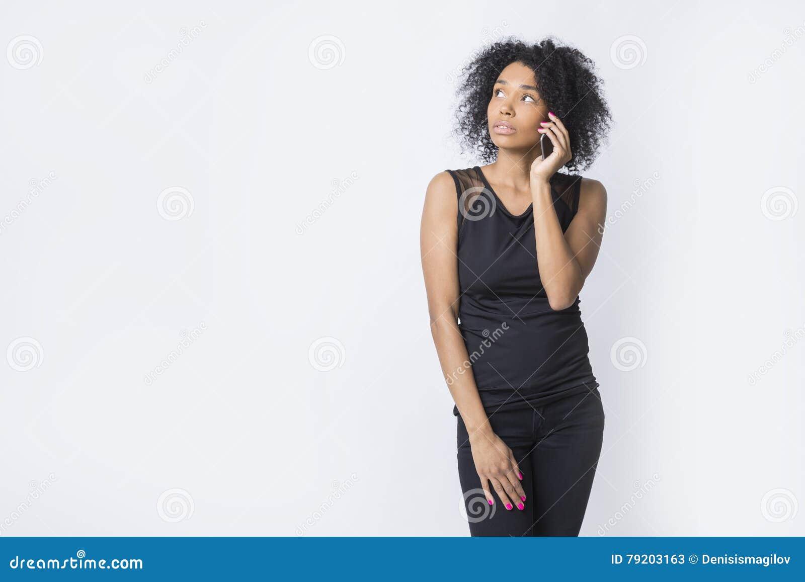 A mulher afro-americano séria está falando em seu telefone